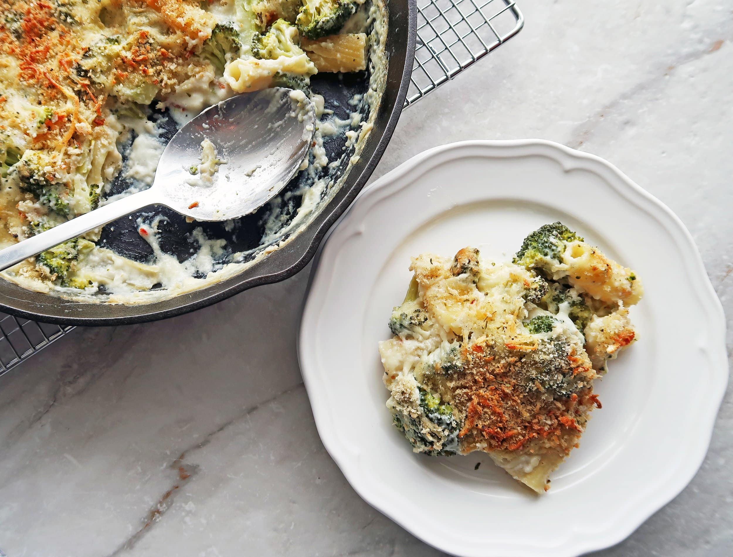 A plate of baked pasta with broccoli and white cheese sauce.