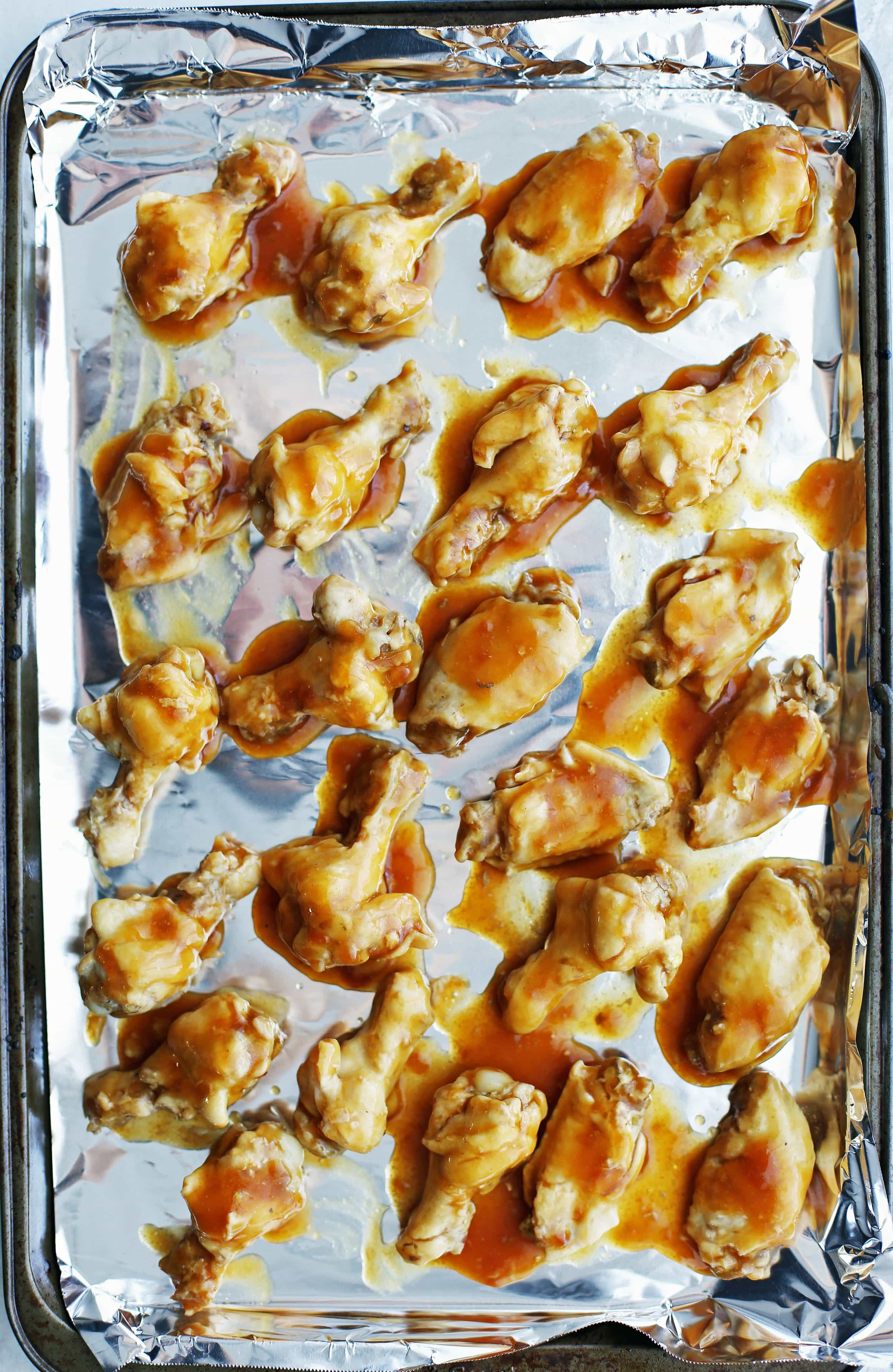 Cooked chicken wings coated with orange teriyaki sauce is placed on a baking sheet in a single layer.