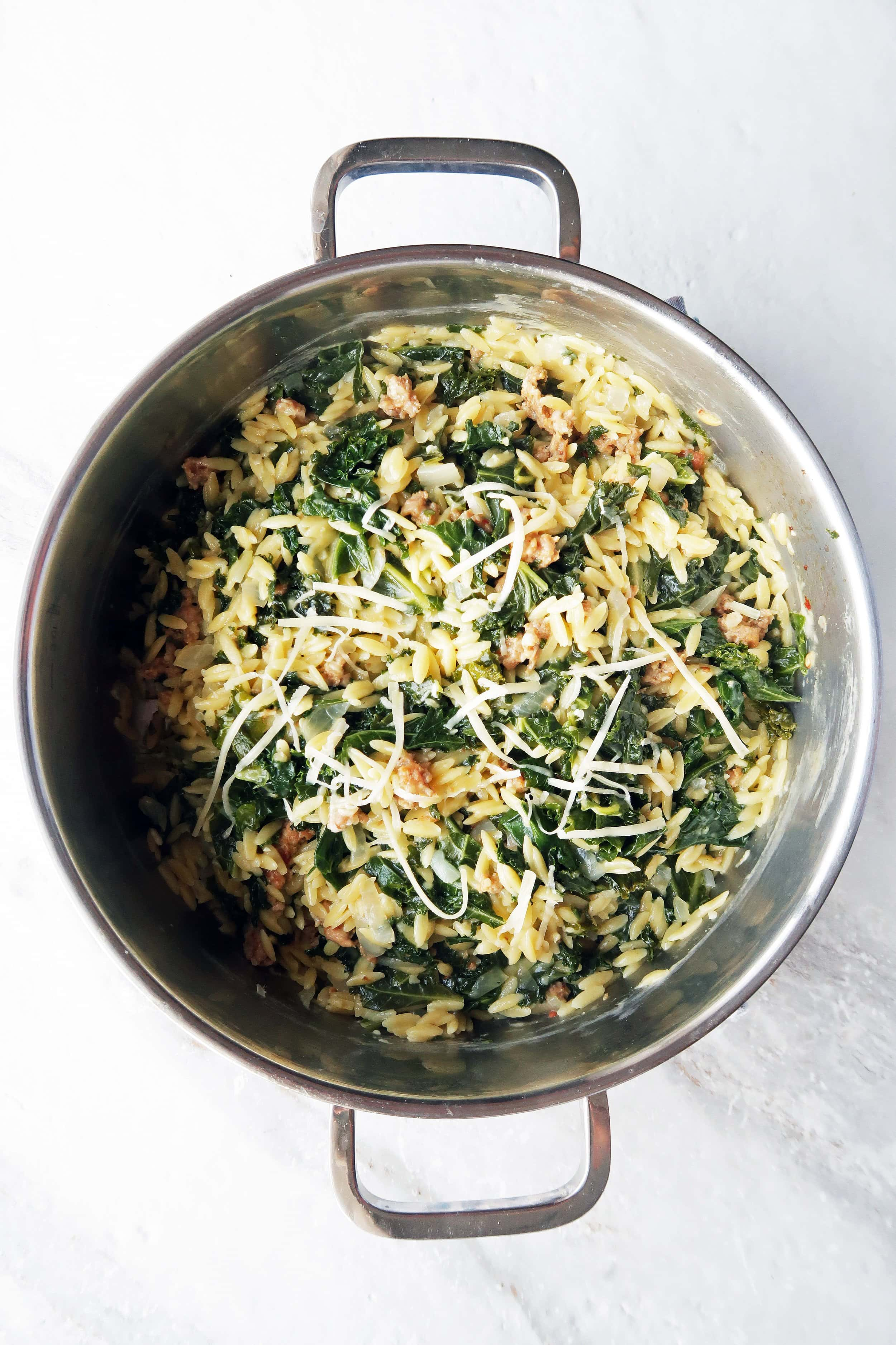 Orzo pasta with Italian sausage and kale with shredded cheese on top in a metal pot.