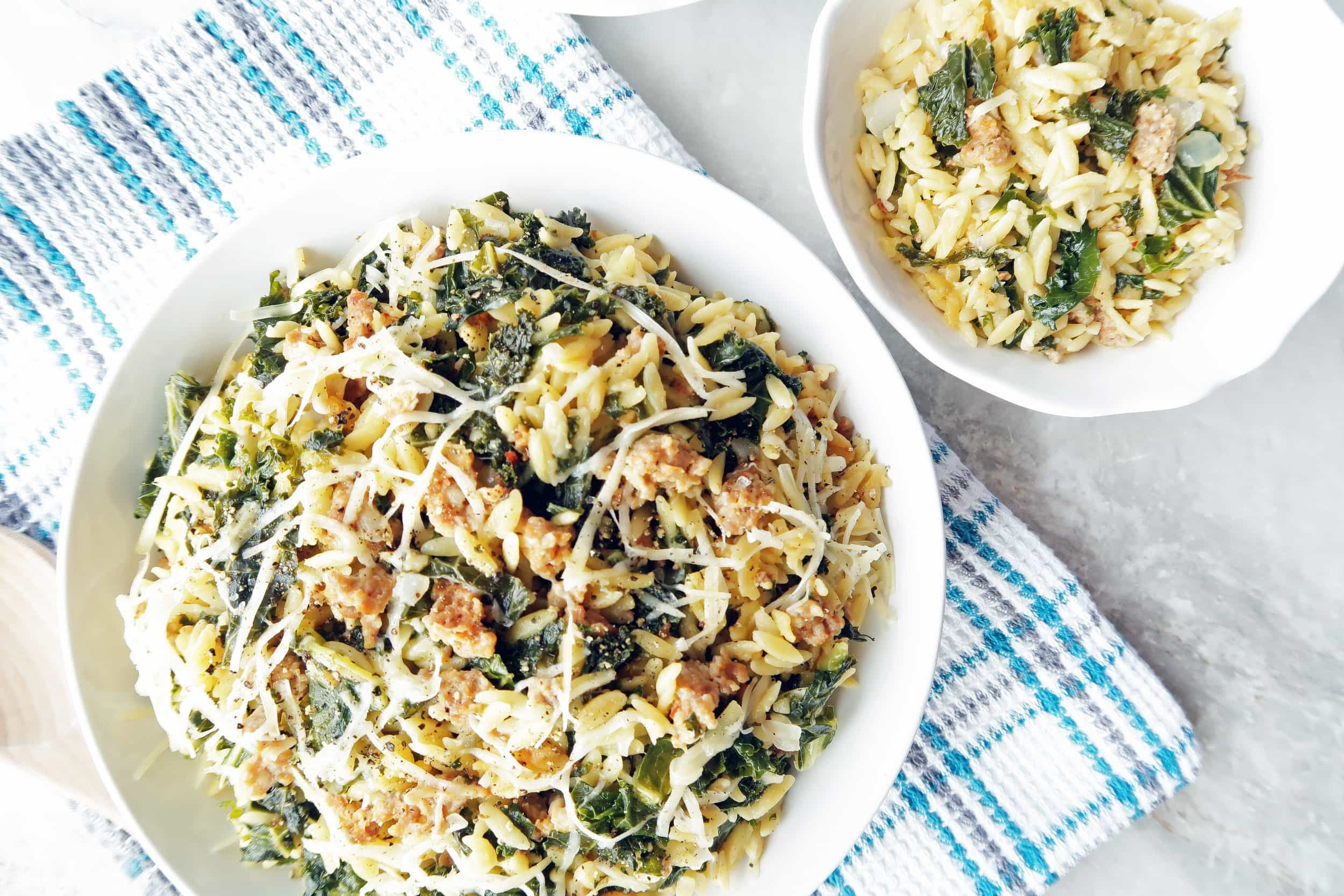 Orzo pasta with Italian sausage and kale in a large pasta bowl and in a small bowl.