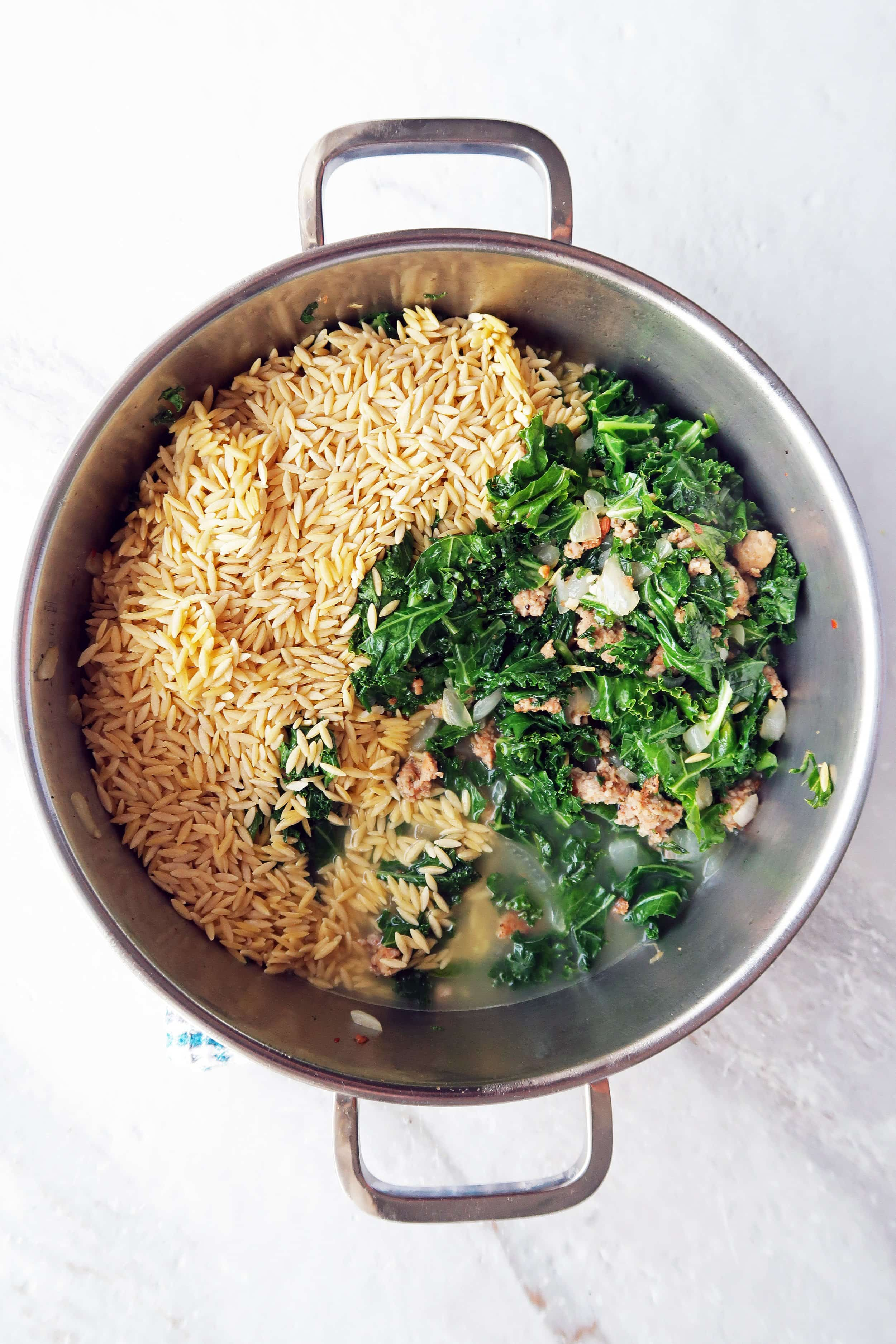 Cooked sausage, sautéed onion, garlic, and kale, broth, and uncooked orzo in a pot.