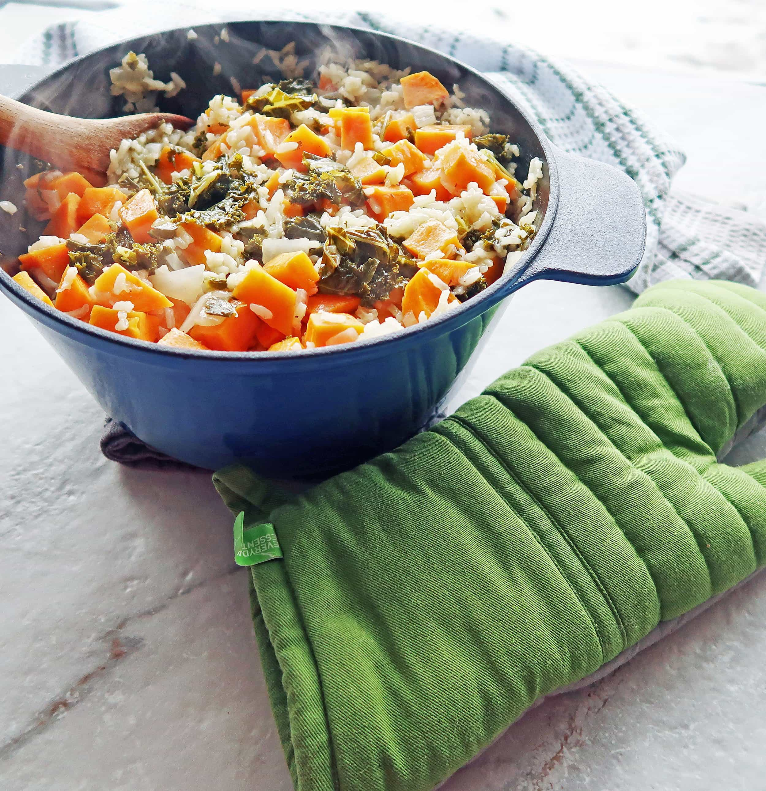 A Dutch oven full of vegetarian, gluten-free sweet potato and kale risotto with green oven mitt to its side.