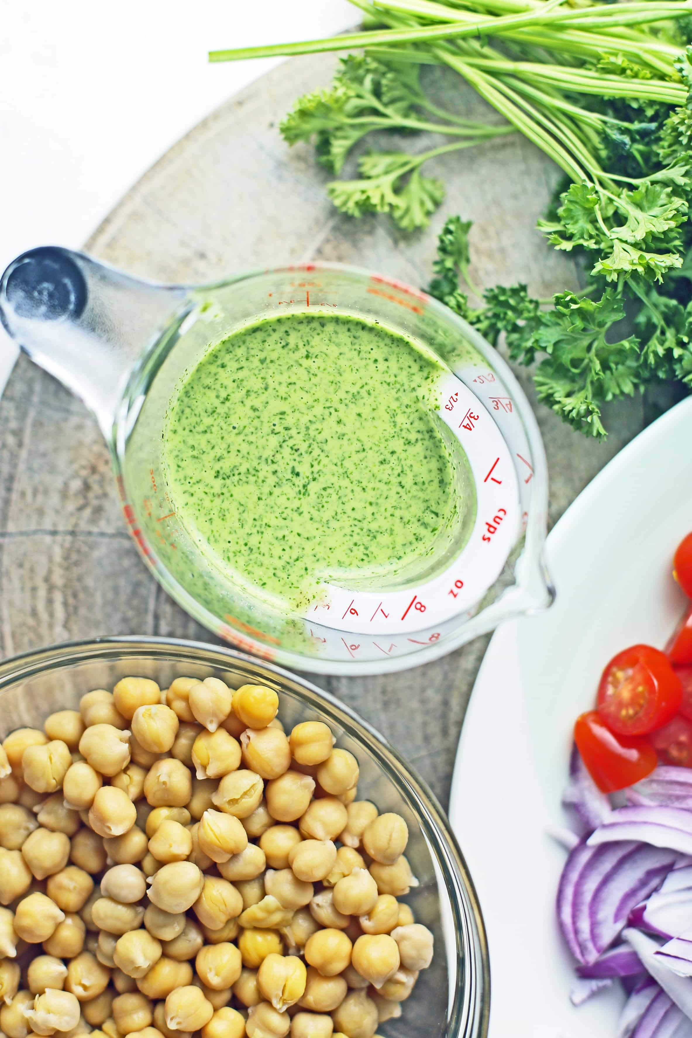 Overhead view of parsley dressing in a measuring cup and cooked chickpeas in a glass bowl.