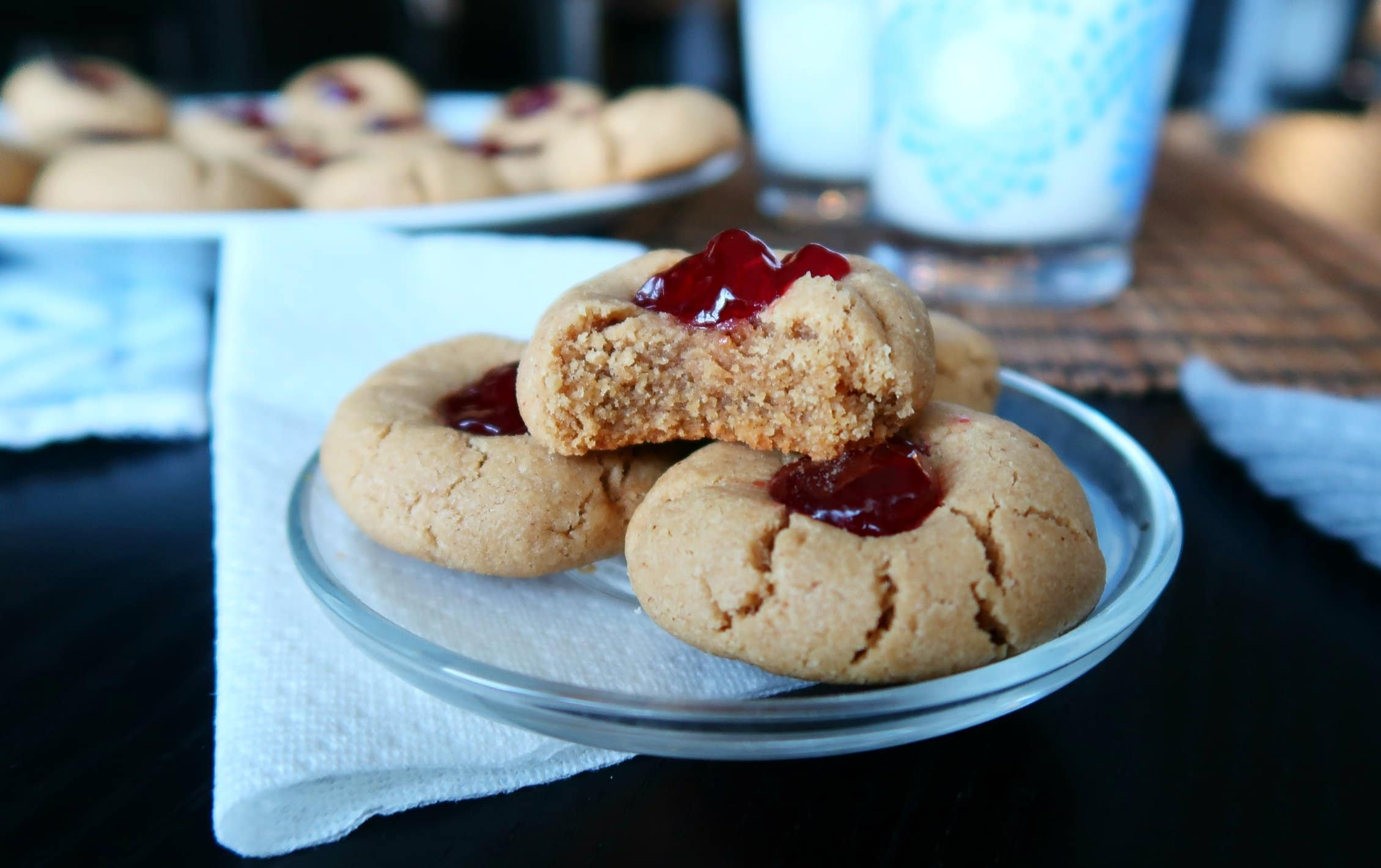 A Peanut Butter and Jelly Thumbprint Cookie with a bite missing.