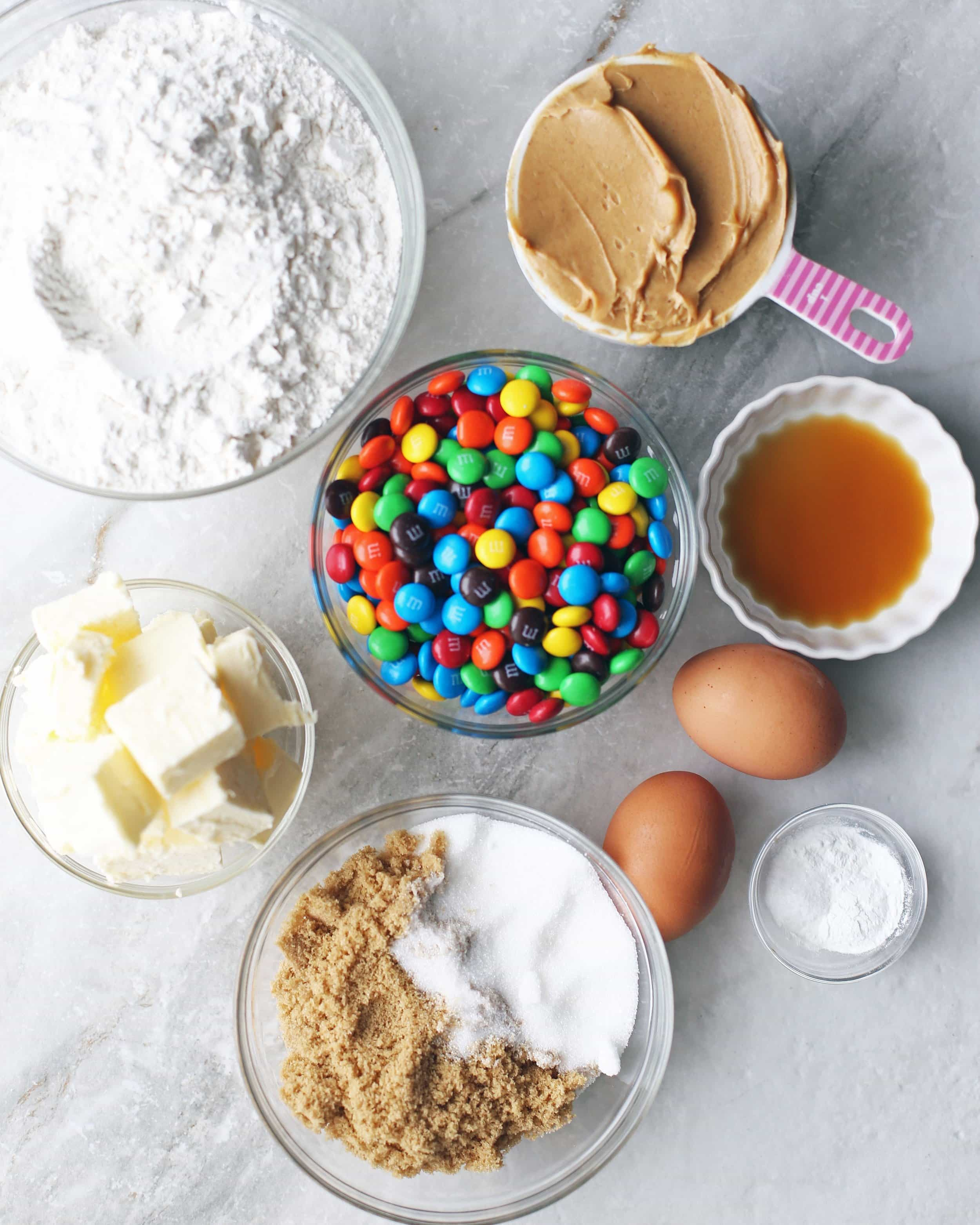 Overhead shot of glass bowls filled with white and brown sugar, butter, flour, peanut butter, vanilla extract, M&M's, eggs, salt, and baking powder.