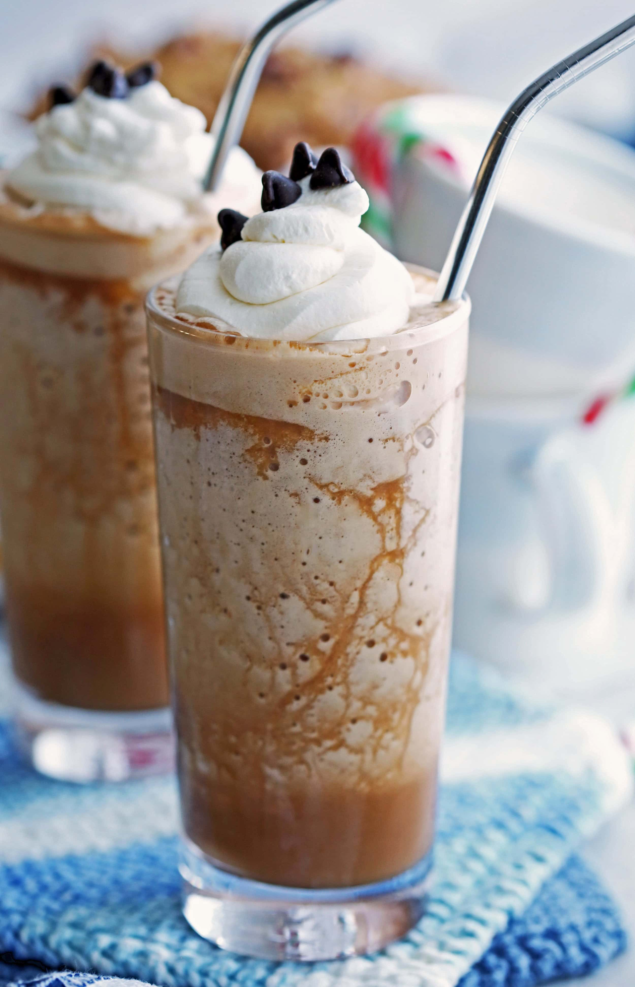 Peppermint mocha frappes topped with whipped cream and chocolate chips in two tall drinking glasses.