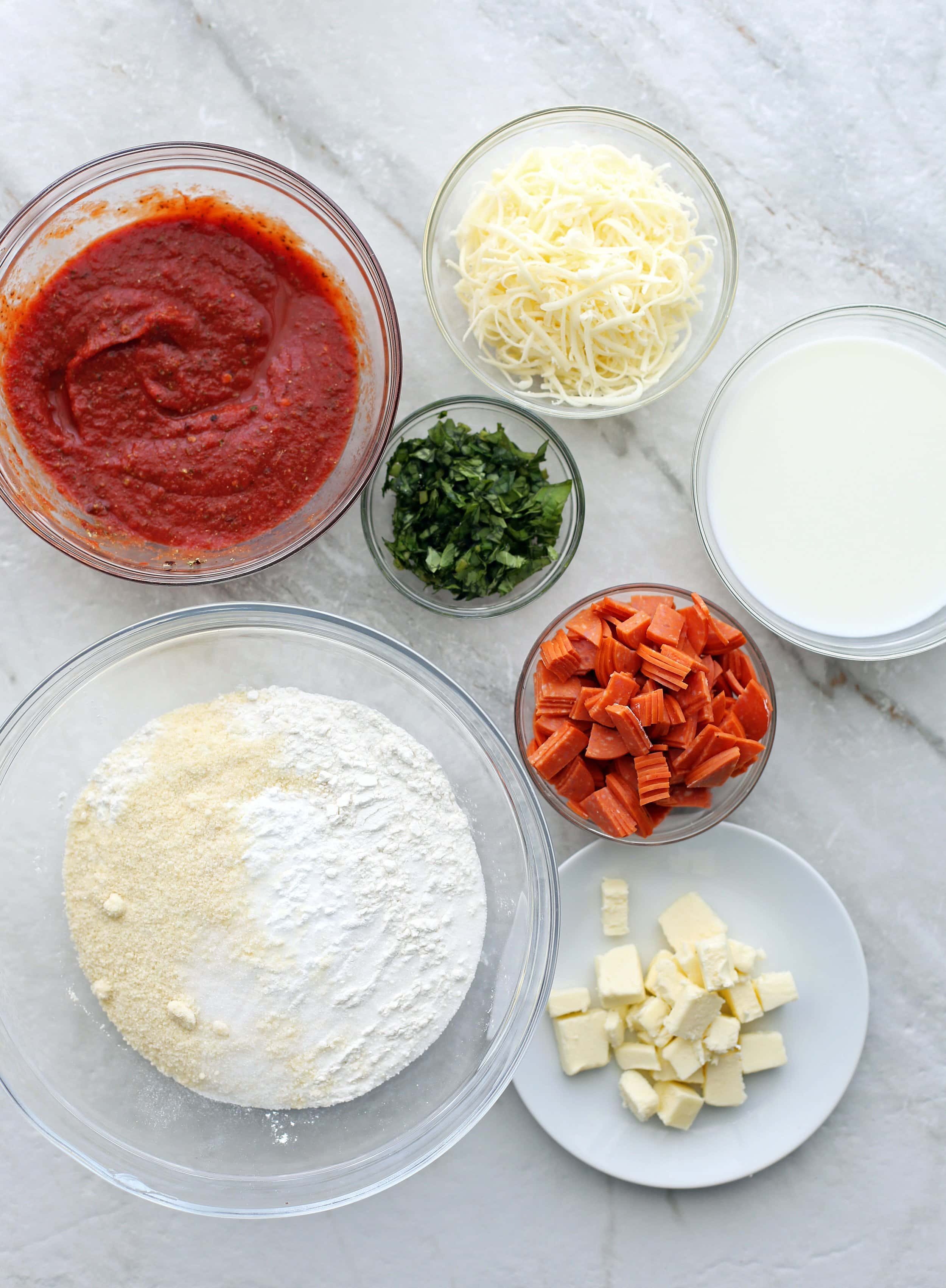 Bowls of pepperoni, cheese, fresh basil, pizza sauce, flour mixture, milk, and butter.
