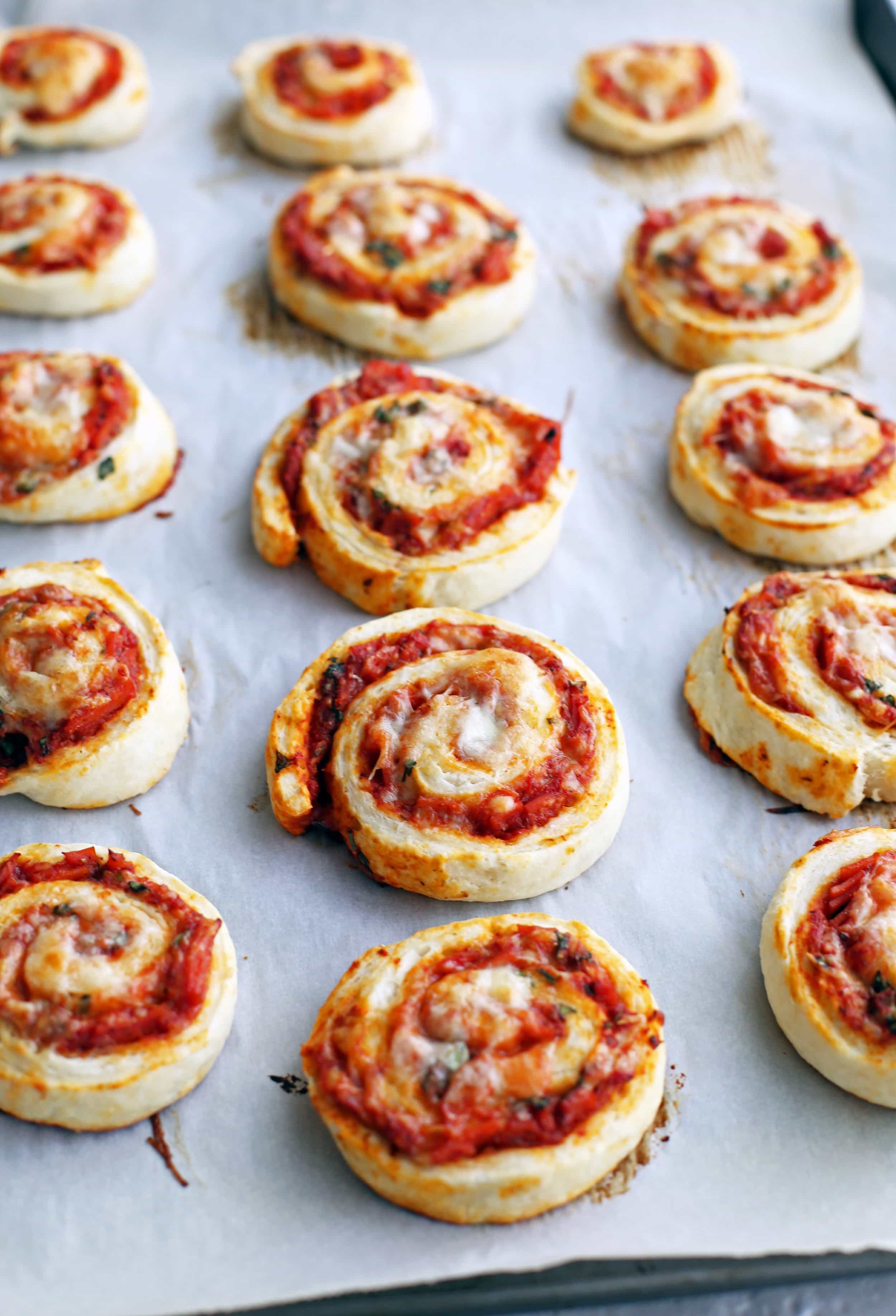 Freshly baked pepperoni cheese pizza rolls on a parchment paper lined baking sheet.