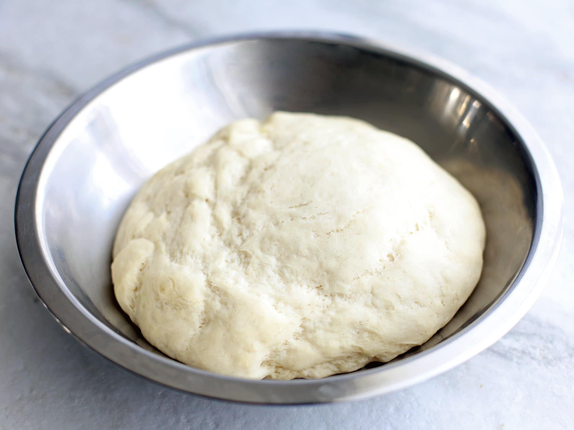 Proved pizza dough in a metal bowl.