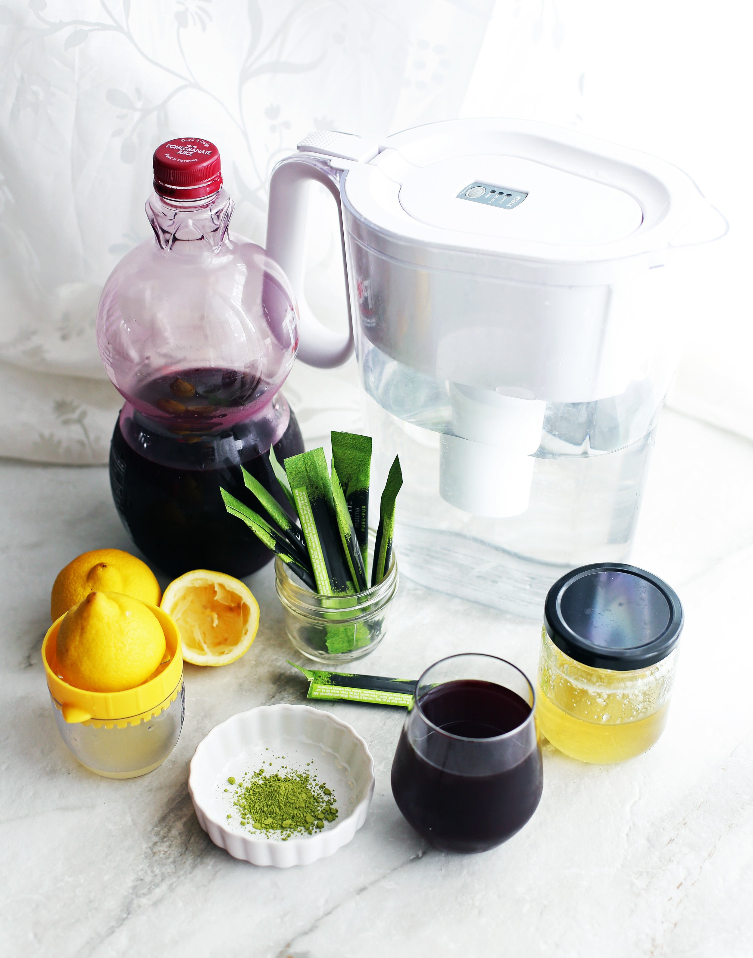 Pomegranate juice, matcha powder, lemon juice, honey, and water on a white surface.