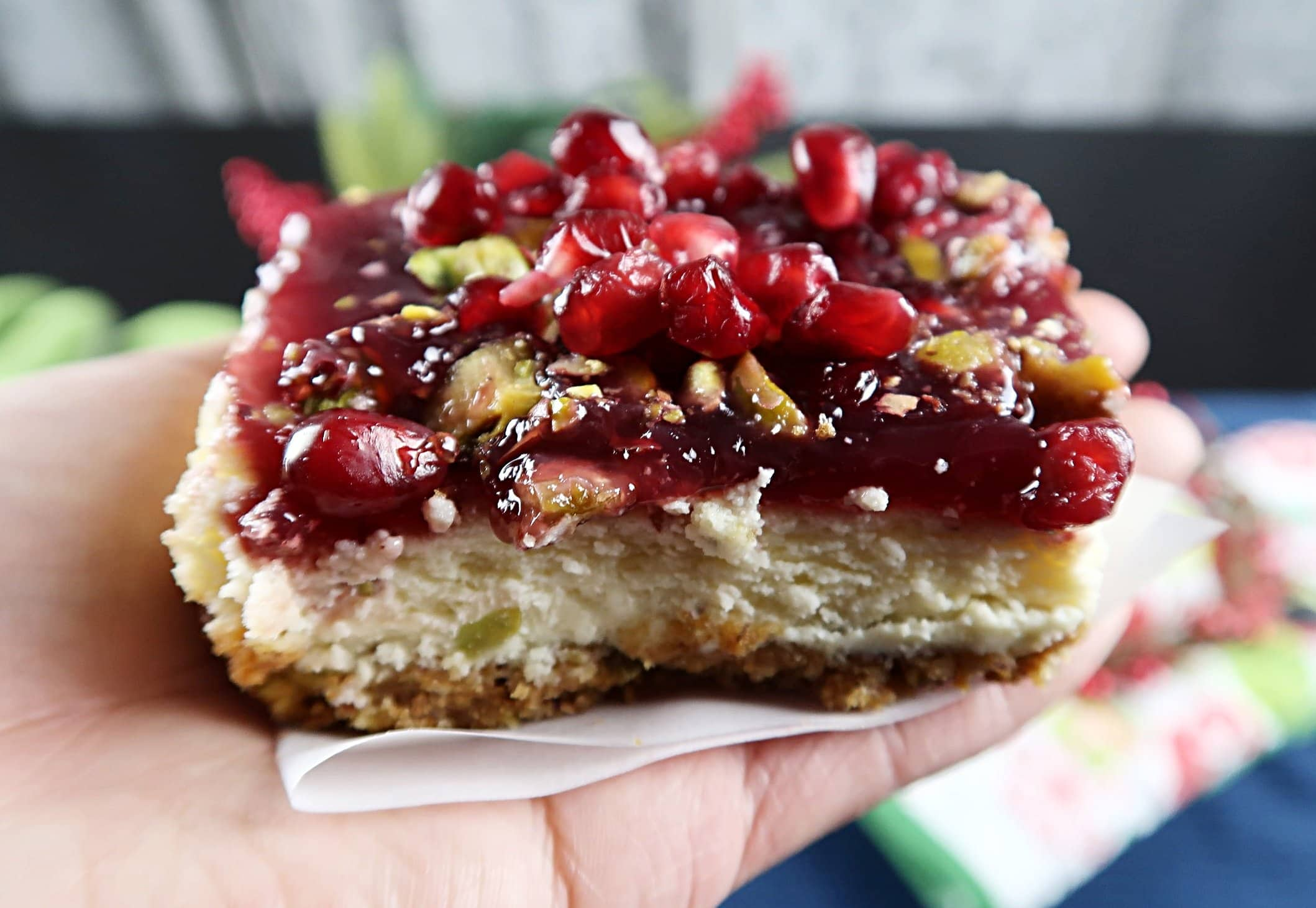 A side view of a pomegranate pistachio cheesecake bar.