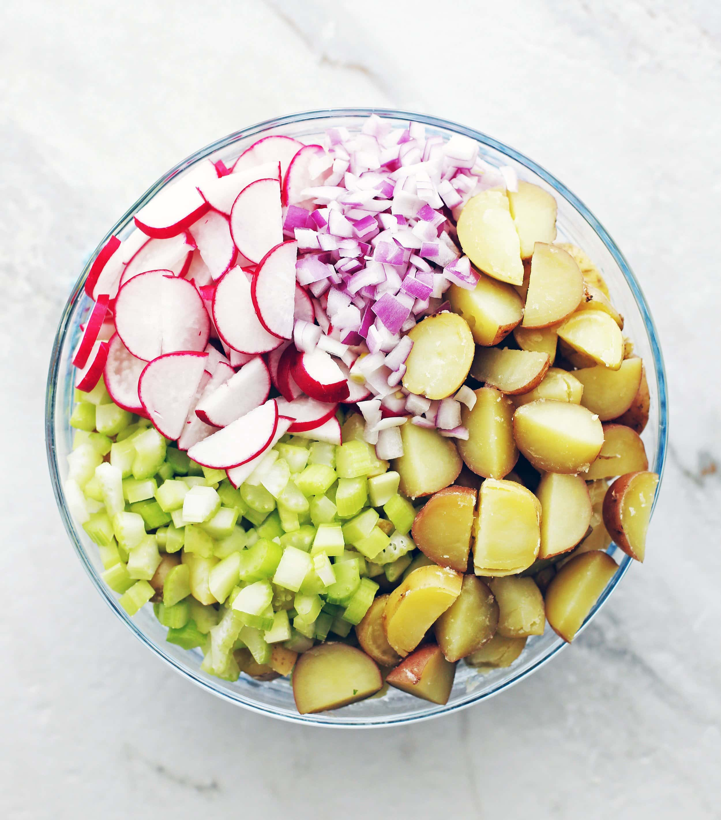 Boiled sliced potatoes, diced celery and red onions, and sliced radishes in a large glass bowl.