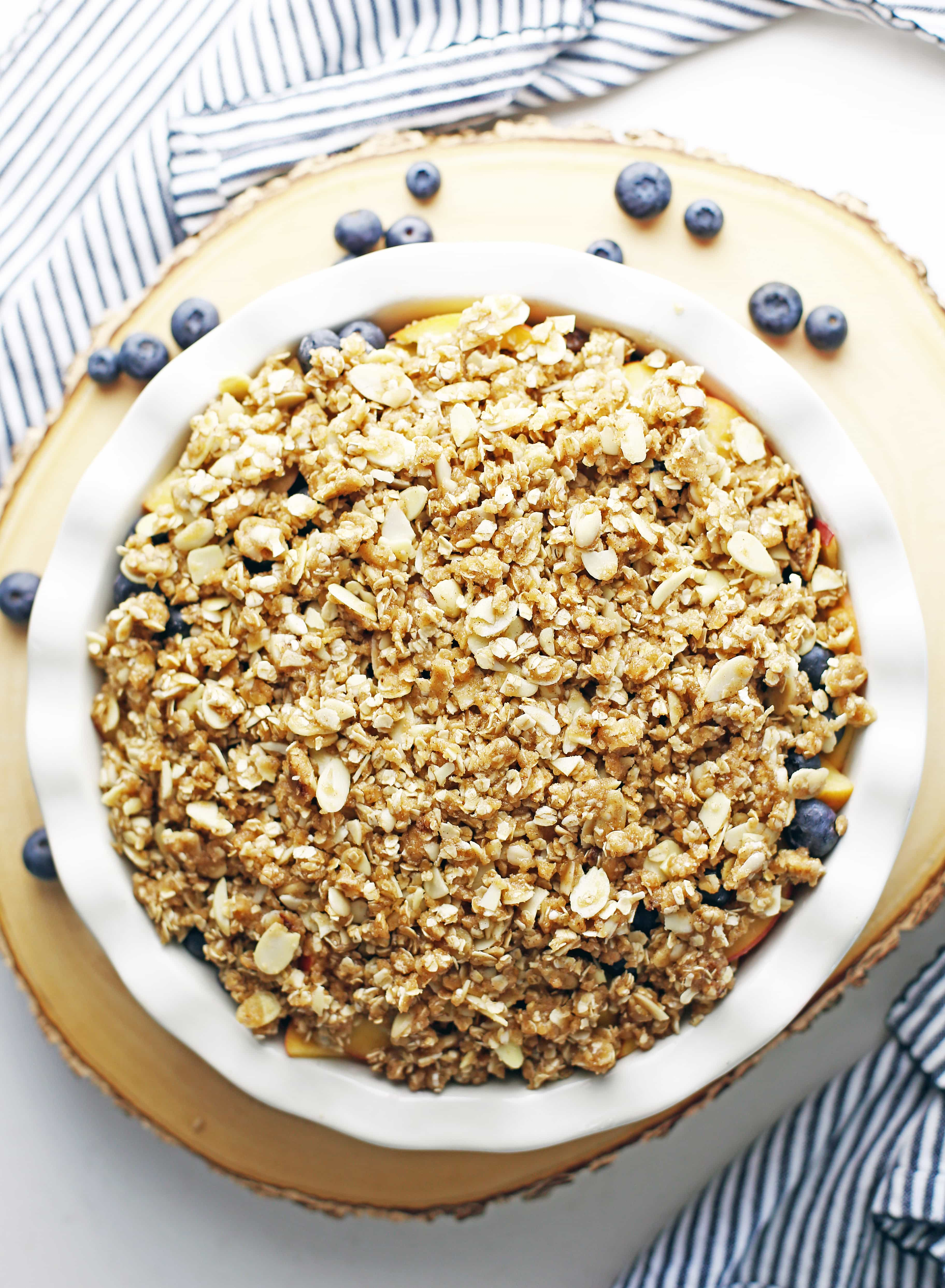 Unbaked peach blueberry crisp with almond oat topping in a round ceramic pie dish.