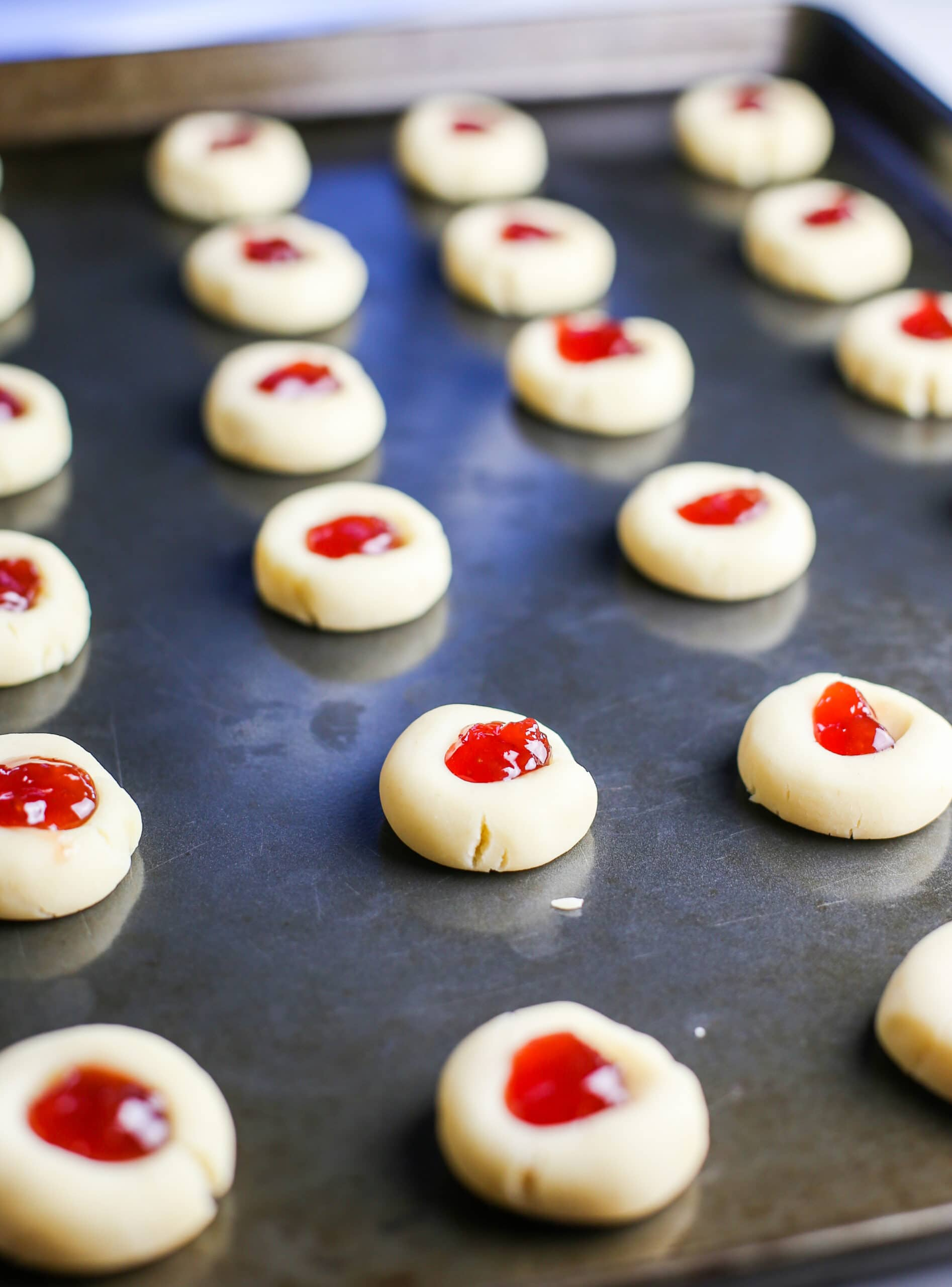 Unbaked condensed milk thumbprint cookies filled with strawberry jam on a baking sheet.
