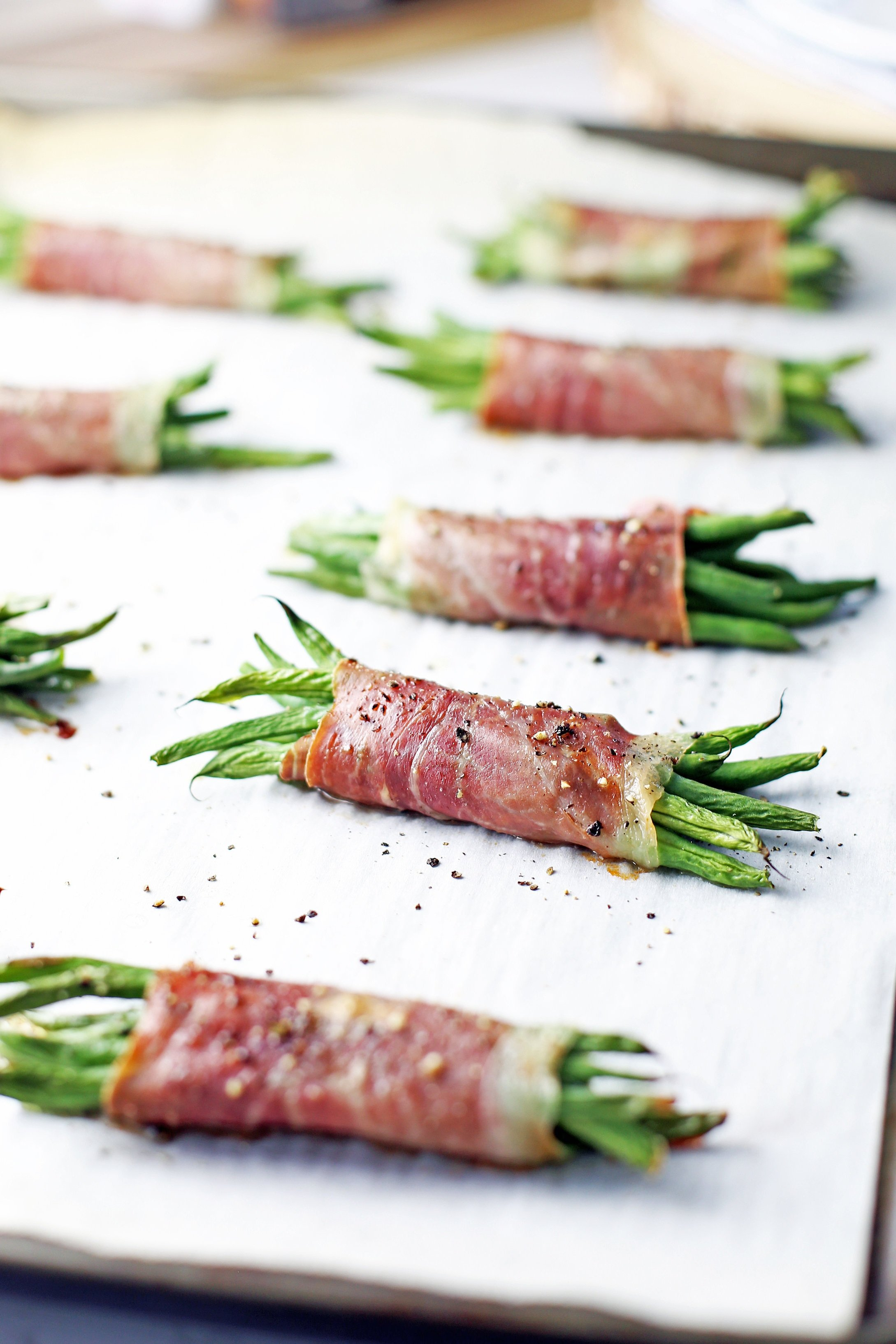 Baked crispy prosciutto wrapped green bean bundles on a large parchment paper-lined baking sheet.