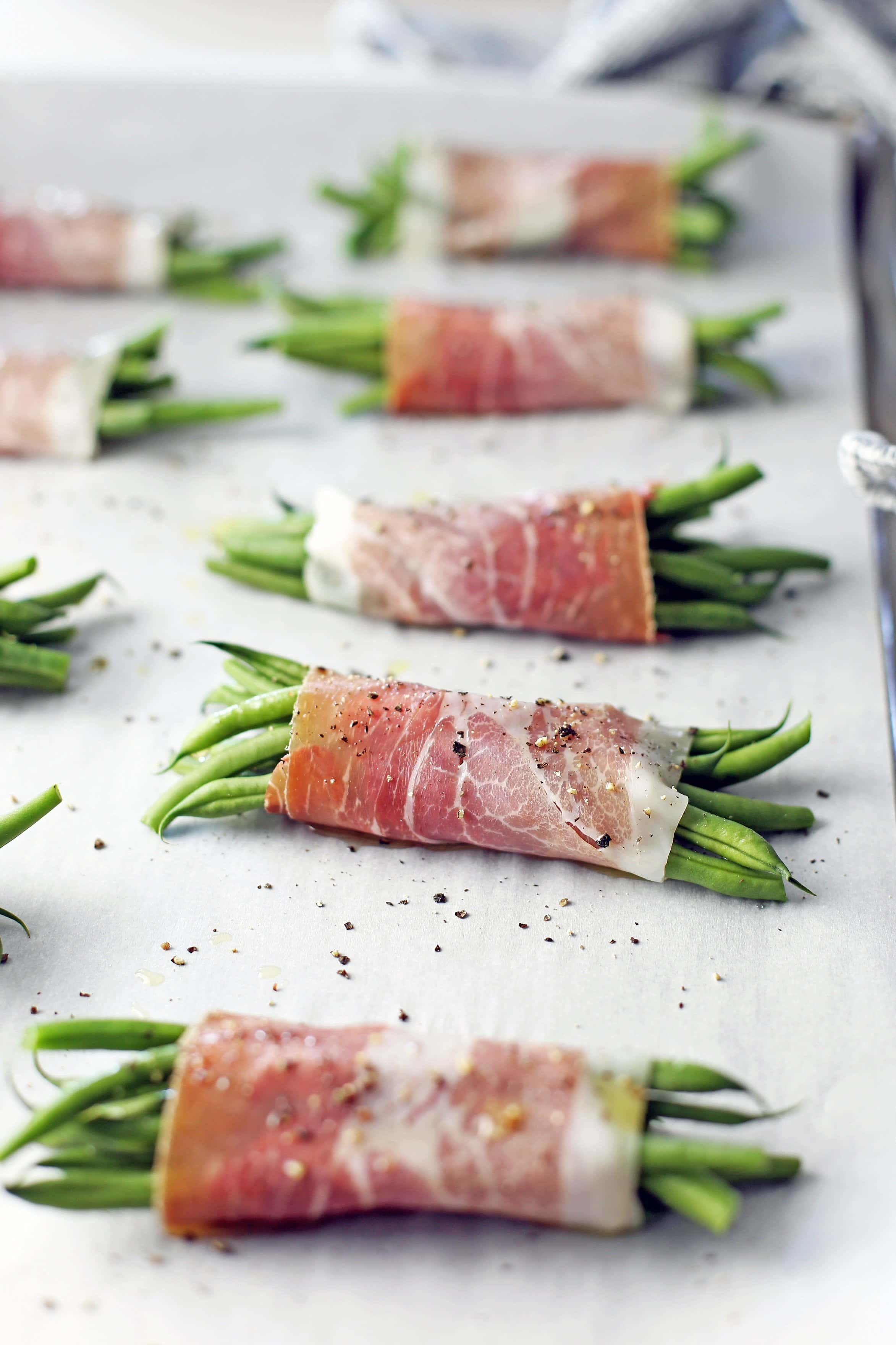 Prosciutto wrapped green beans on a large parchment paper-lined baking sheet in a single layer.