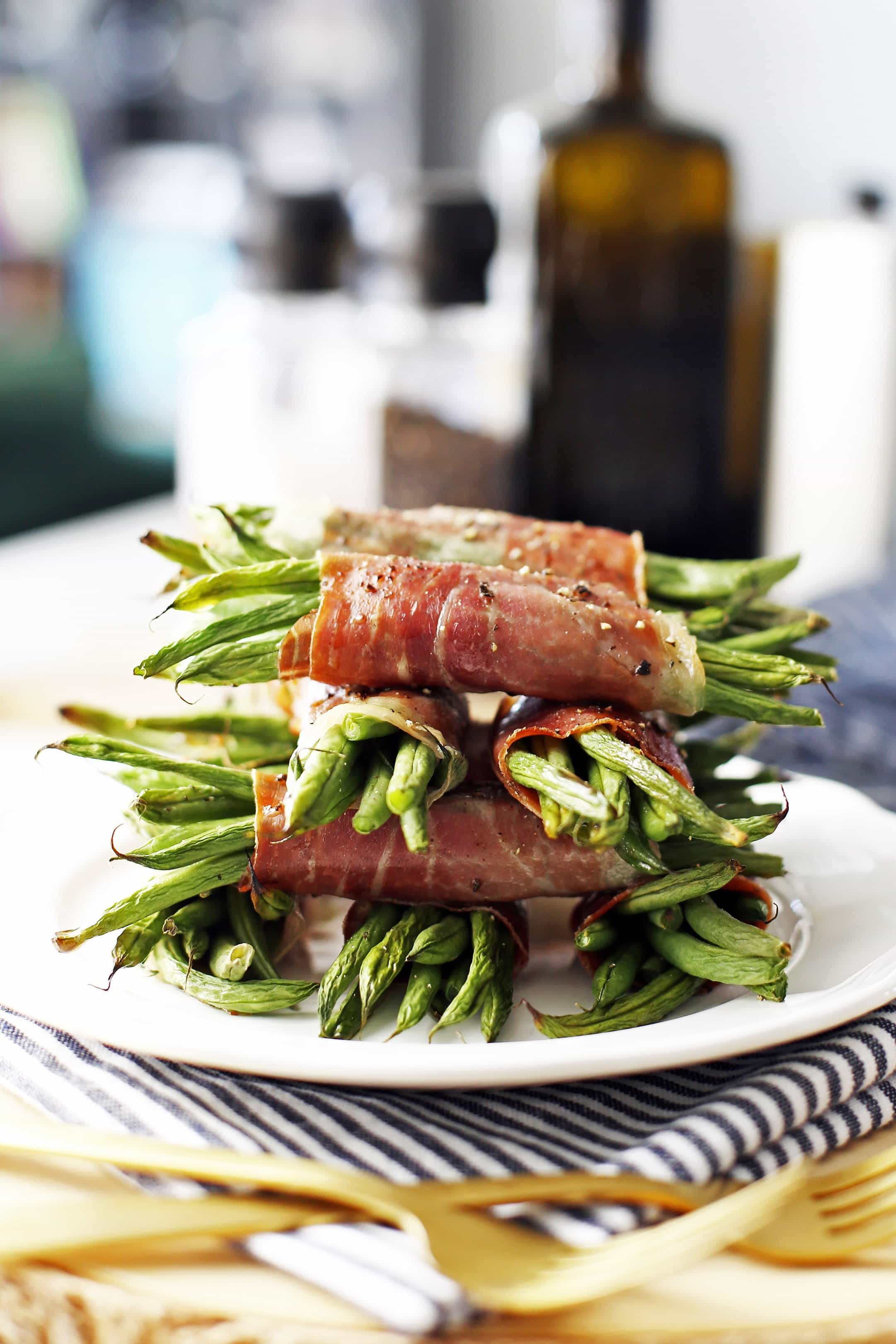 A side view of neatly stacked prosciutto wrapped green bean bundles on a white plate.