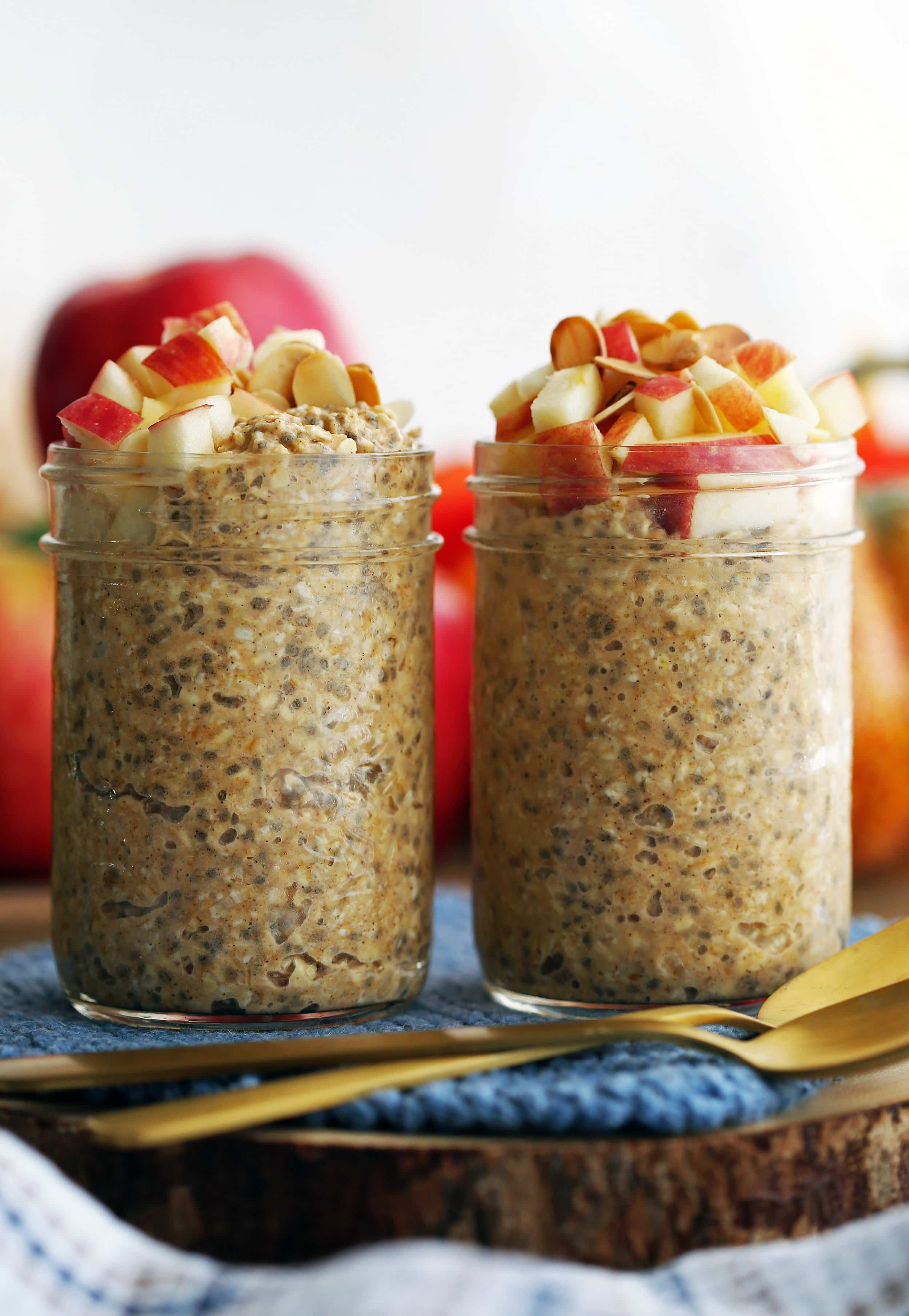 Closeup side view of two jars full of chai spiced pumpkin overnight oats with apple and almond topping.