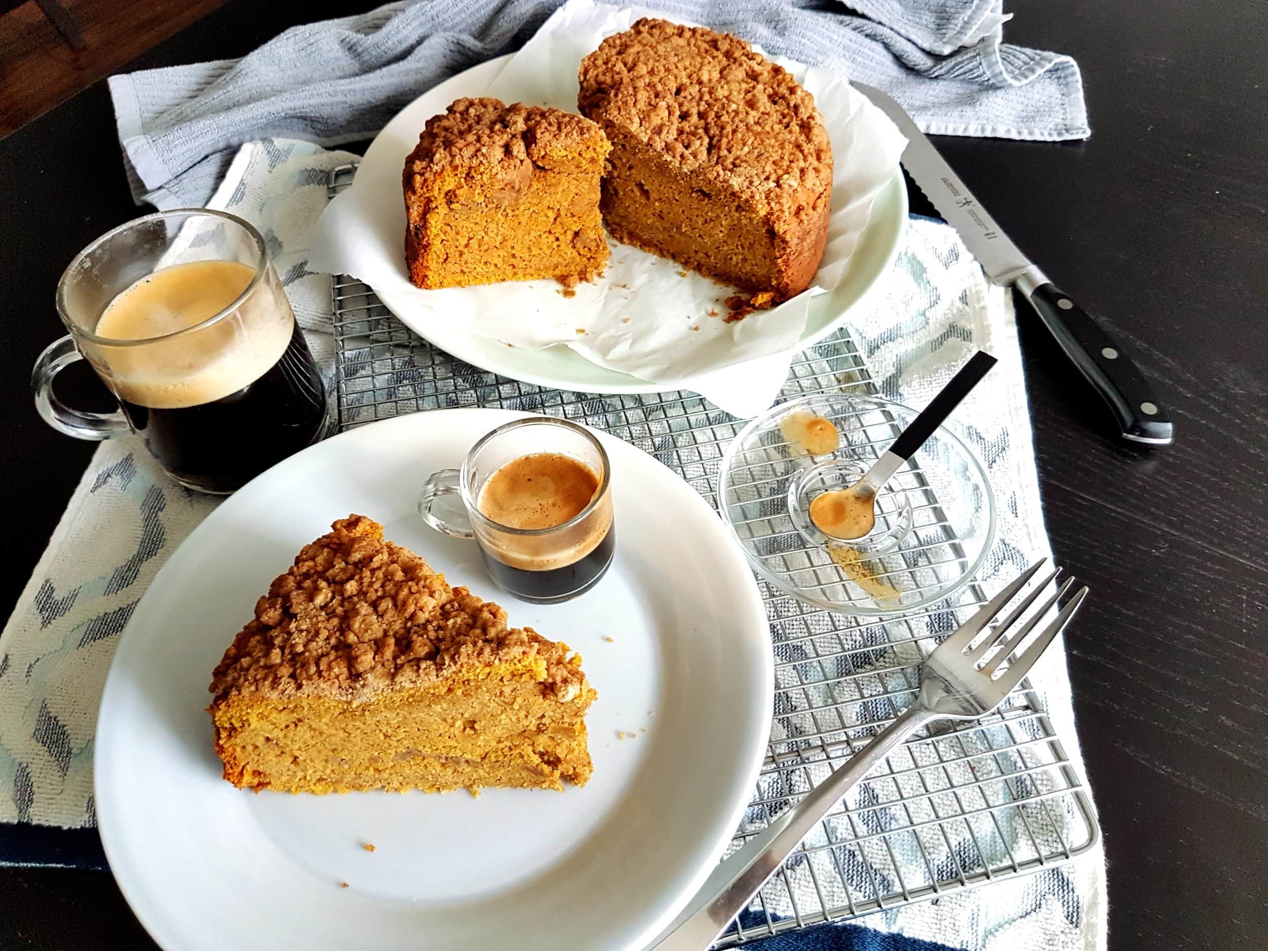A slice of Pumpkin Sour Cream Coffee Cake with a cup of coffee.