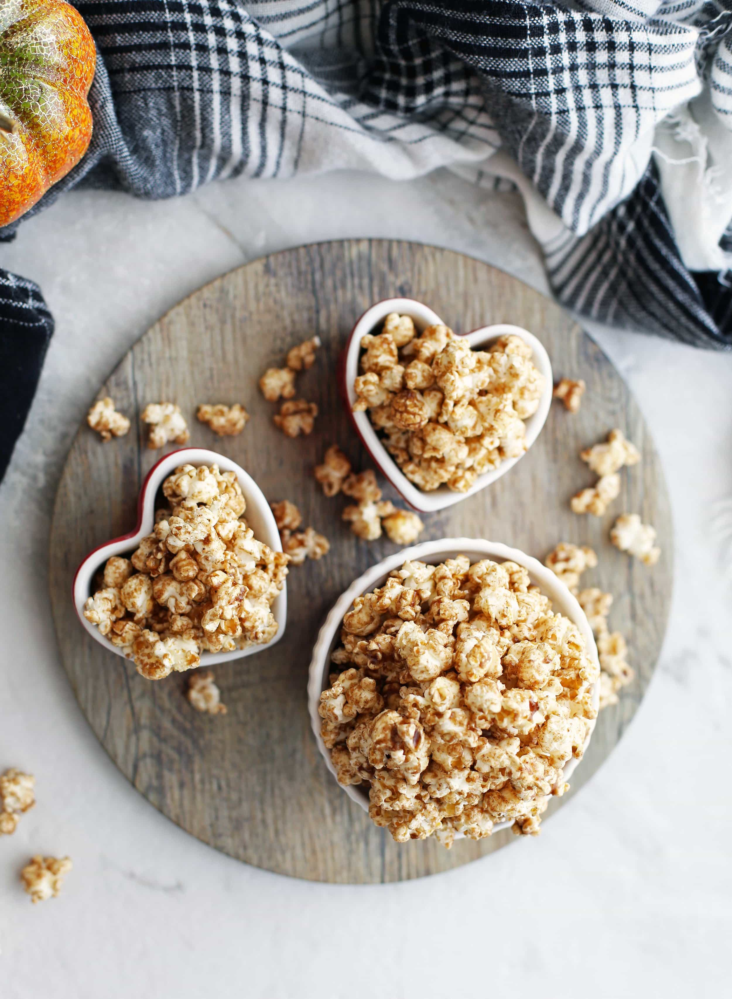 Overhead view of homemade pumpkin spice butterscotch popcorn in three bowls.
