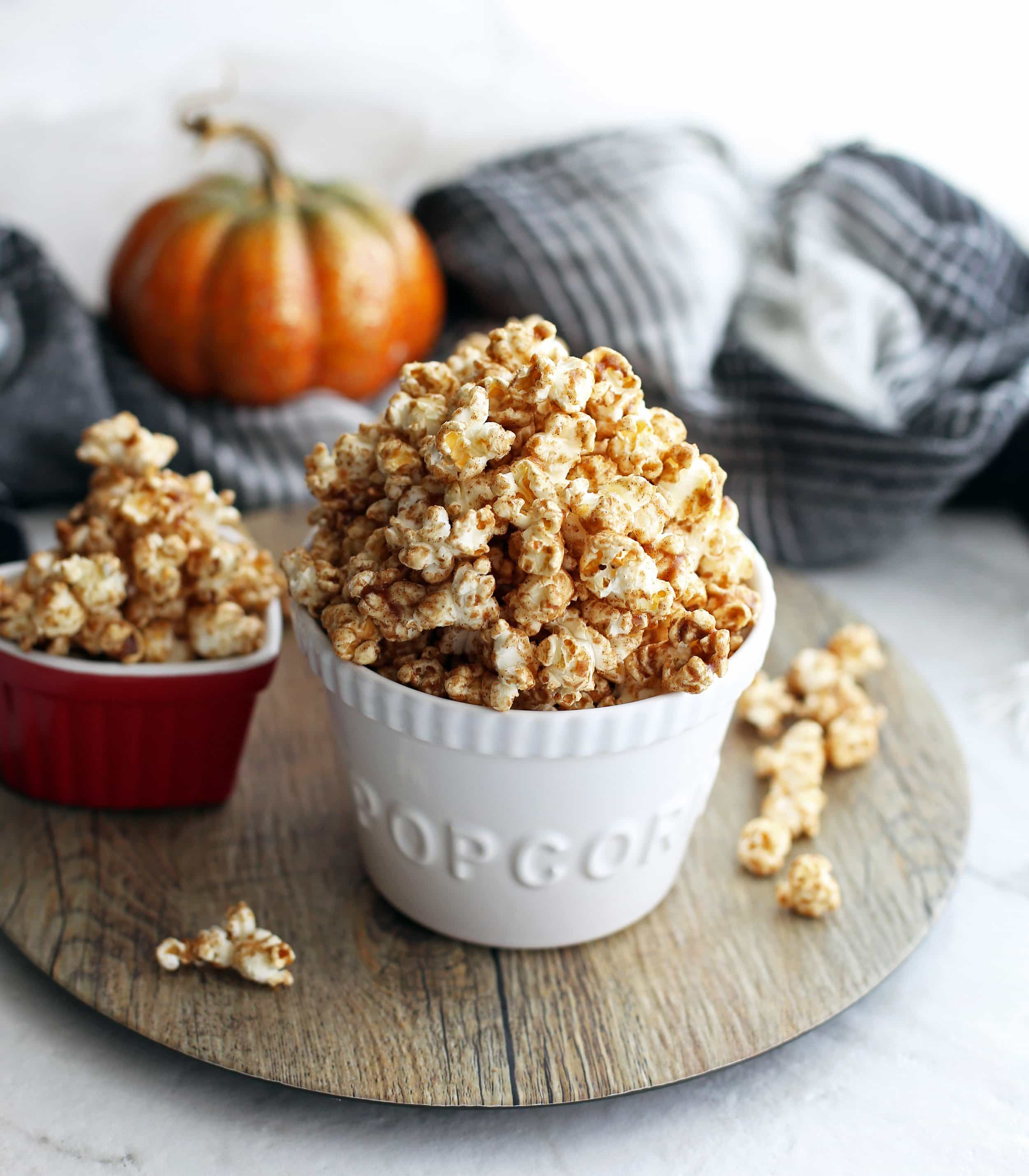 Two bowls filled with homemade pumpkin spice butterscotch popcorn on a wooden platter.