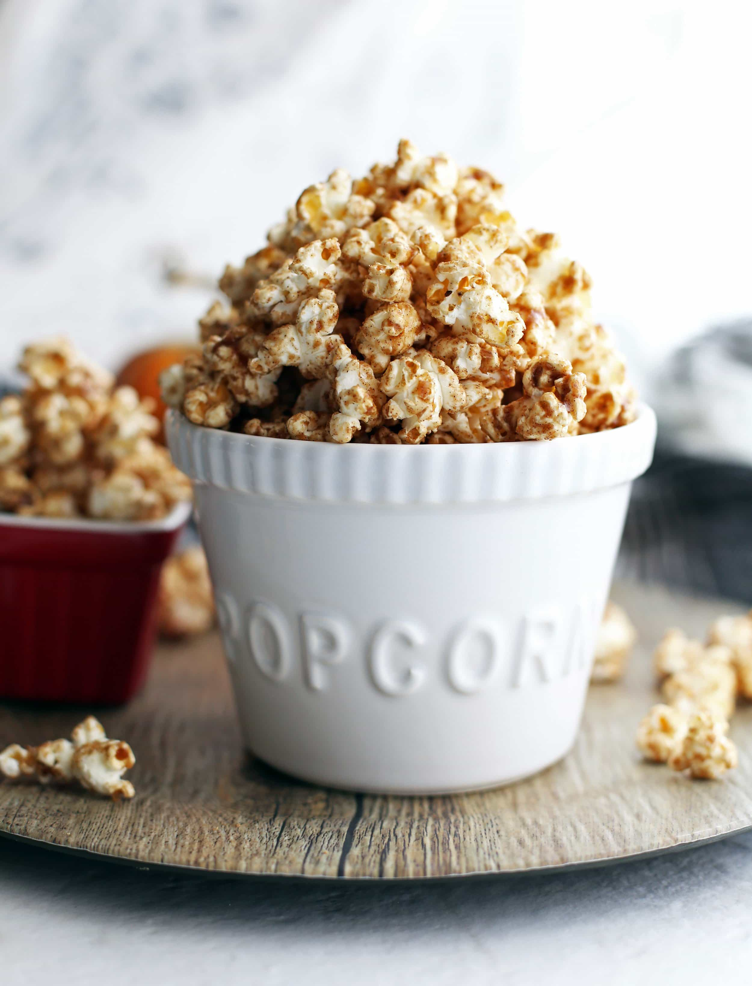 Close-up side view of homemade pumpkin spice butterscotch popcorn in a white bowl.