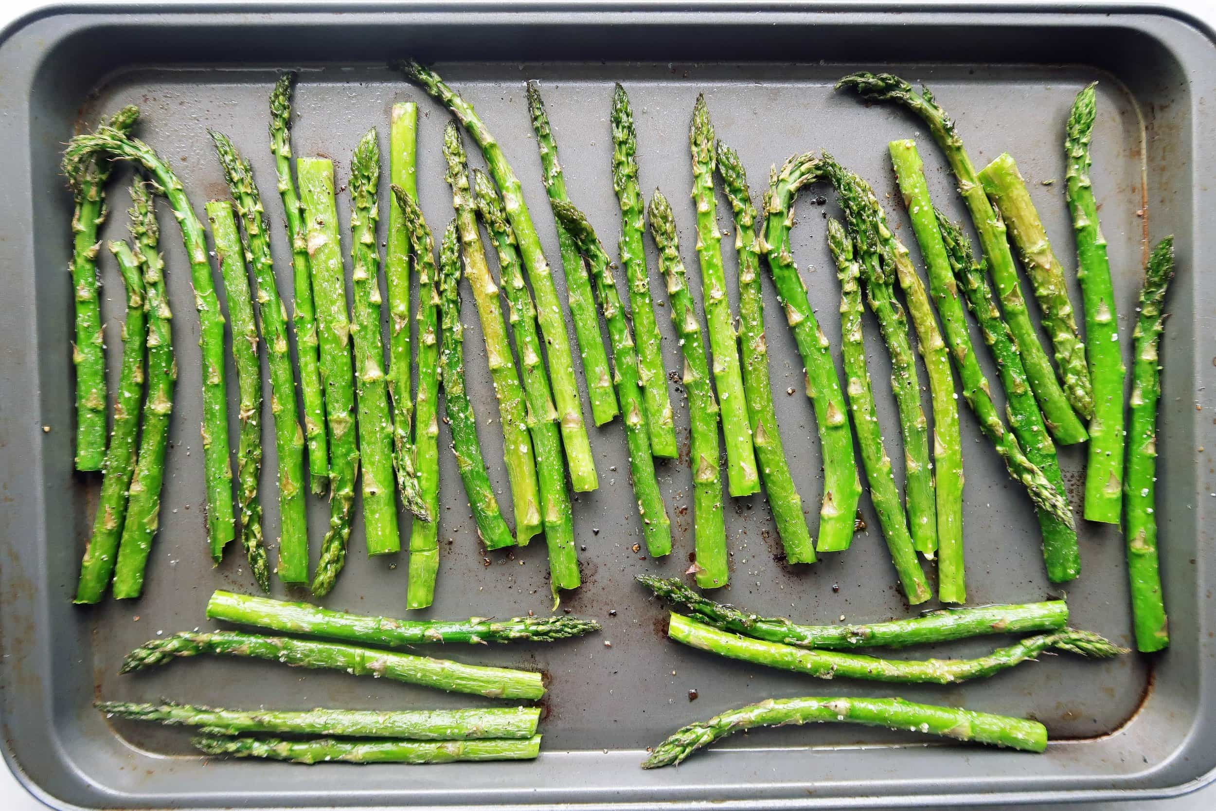 Asparagus coated with olive oil, salt, and pepper, lined up on a sheet pan, ready for roasting.