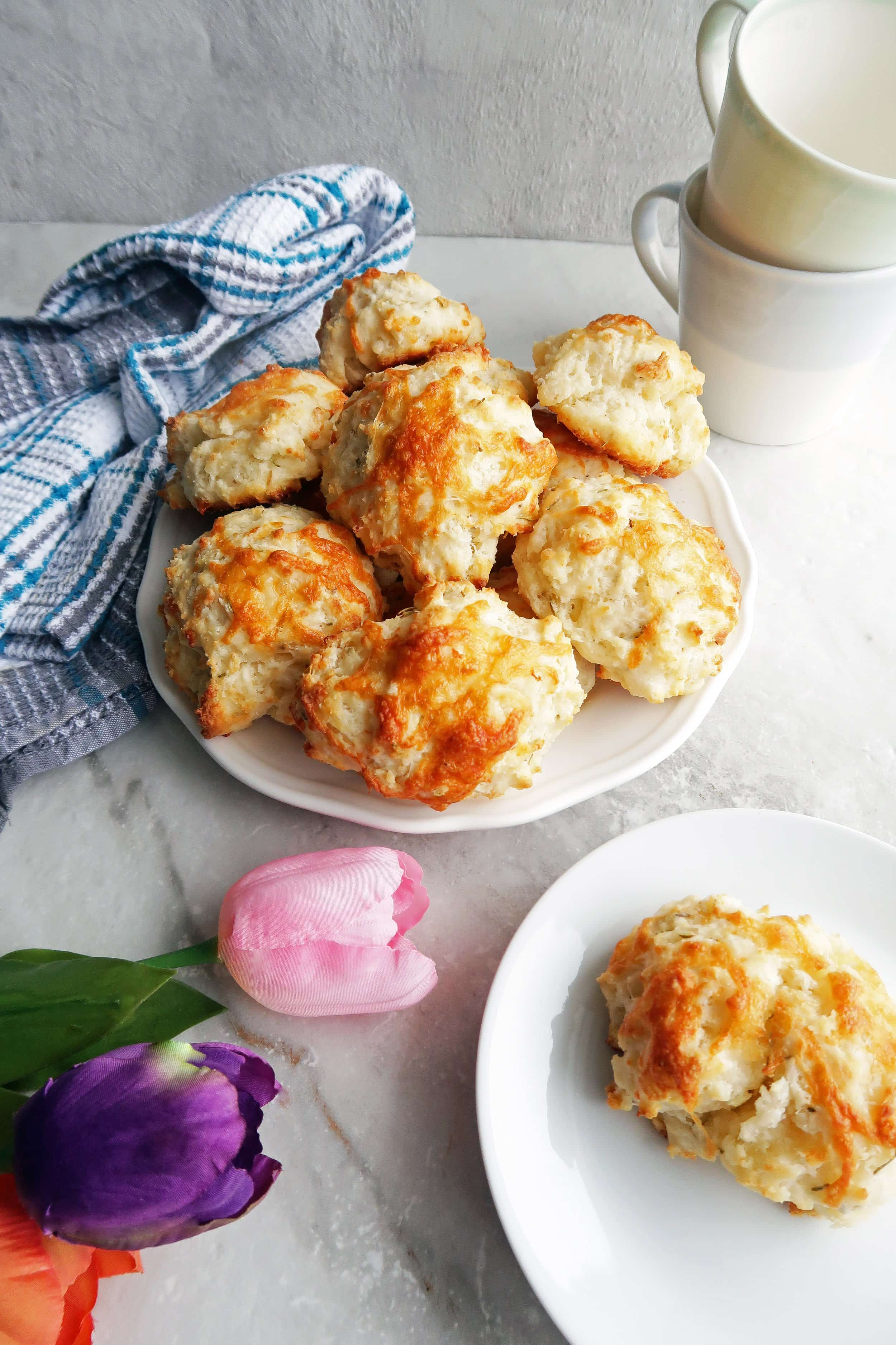 Quick Rosemary Cheddar Drop Biscuits piled on a white plate along with a single biscuit on a plate,tulips, a kitchen towel, and cups.