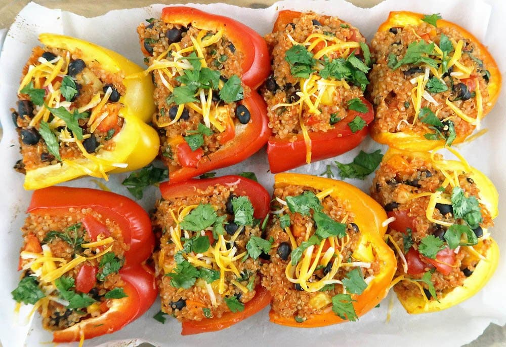 Quinoa and Black Bean Stuffed Bell Peppers topped with cheese and cilantro.