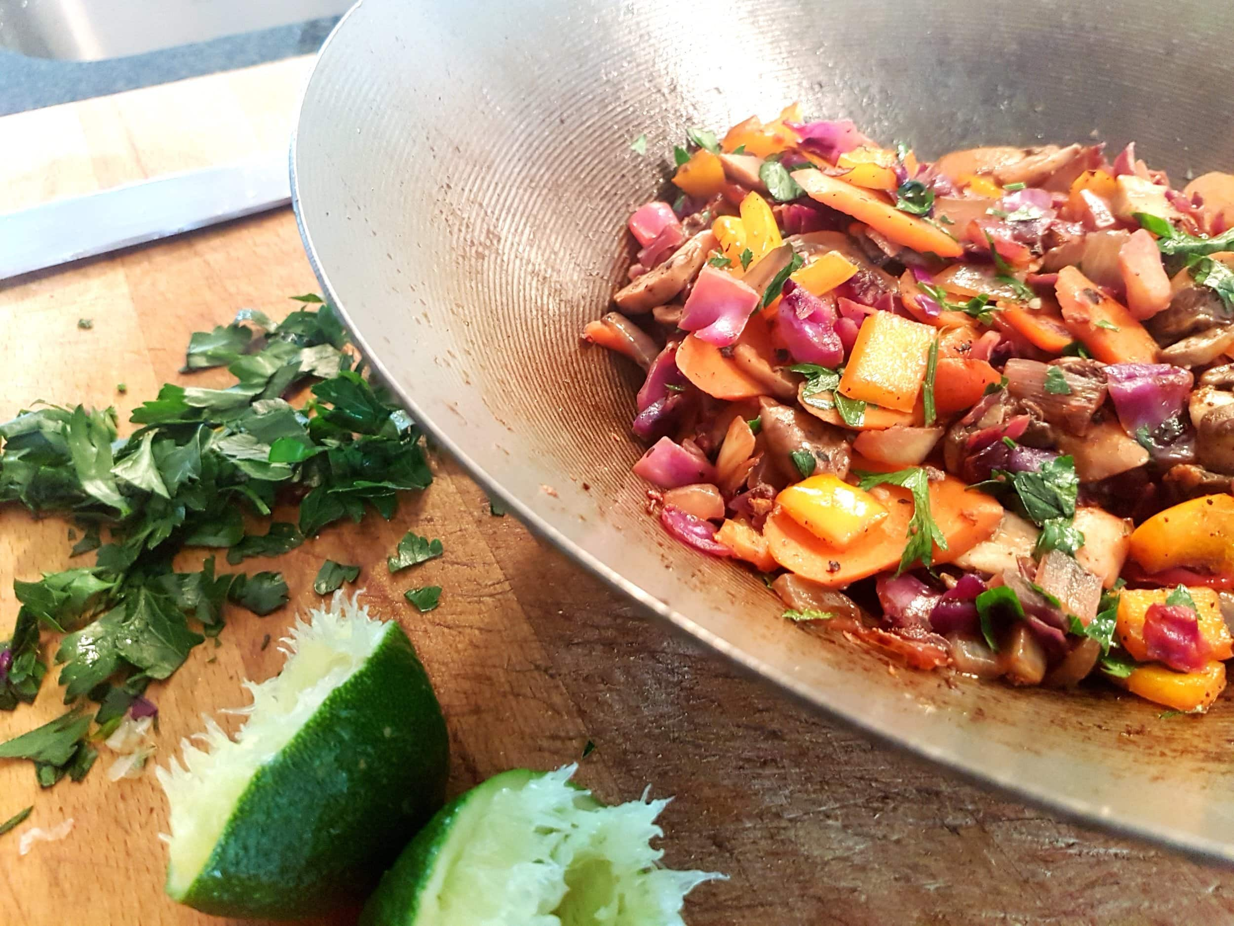 Freshly cooked vegetables in a wok with parsley and lime.