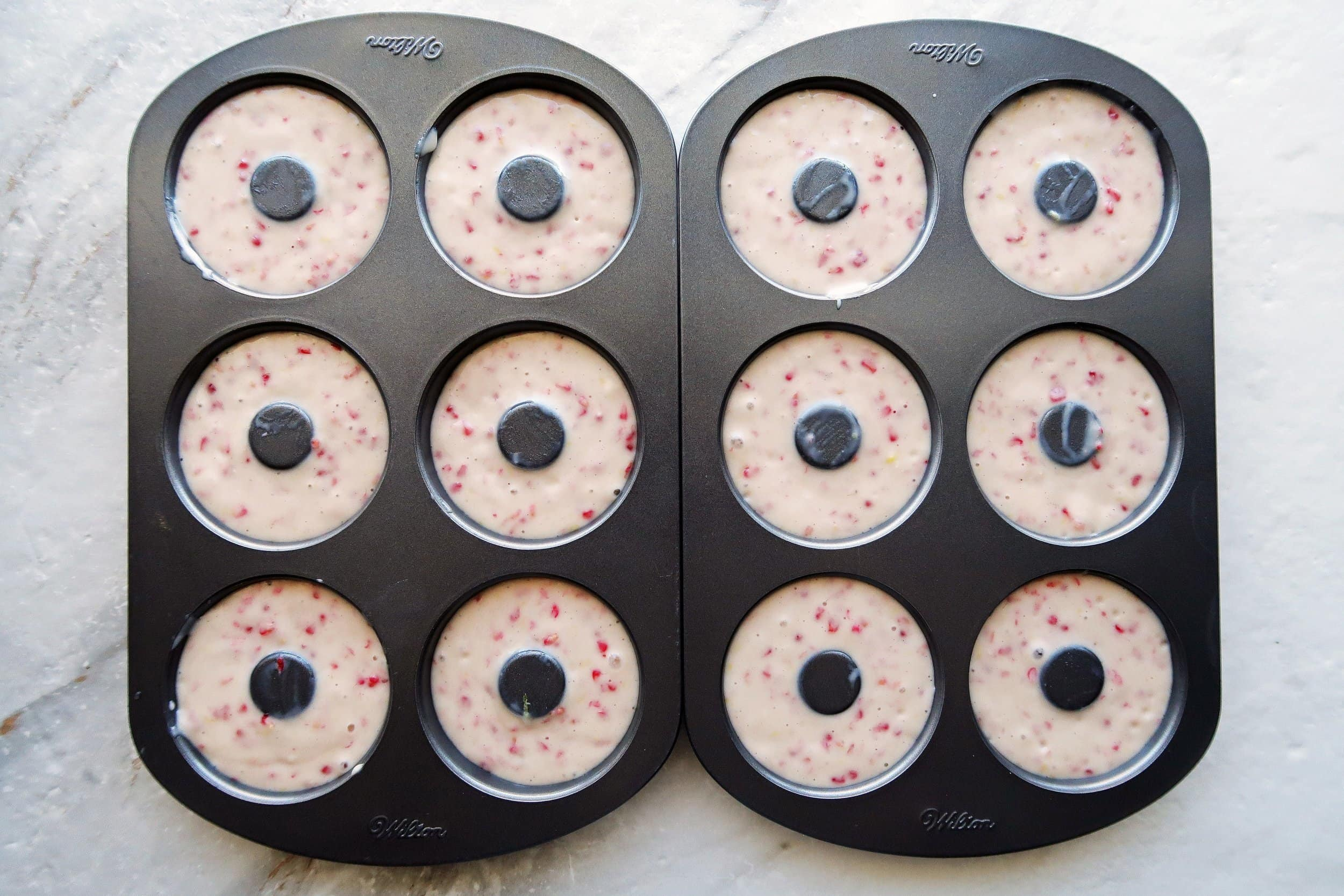 Donut pans filled with raspberry lemon donut batter.