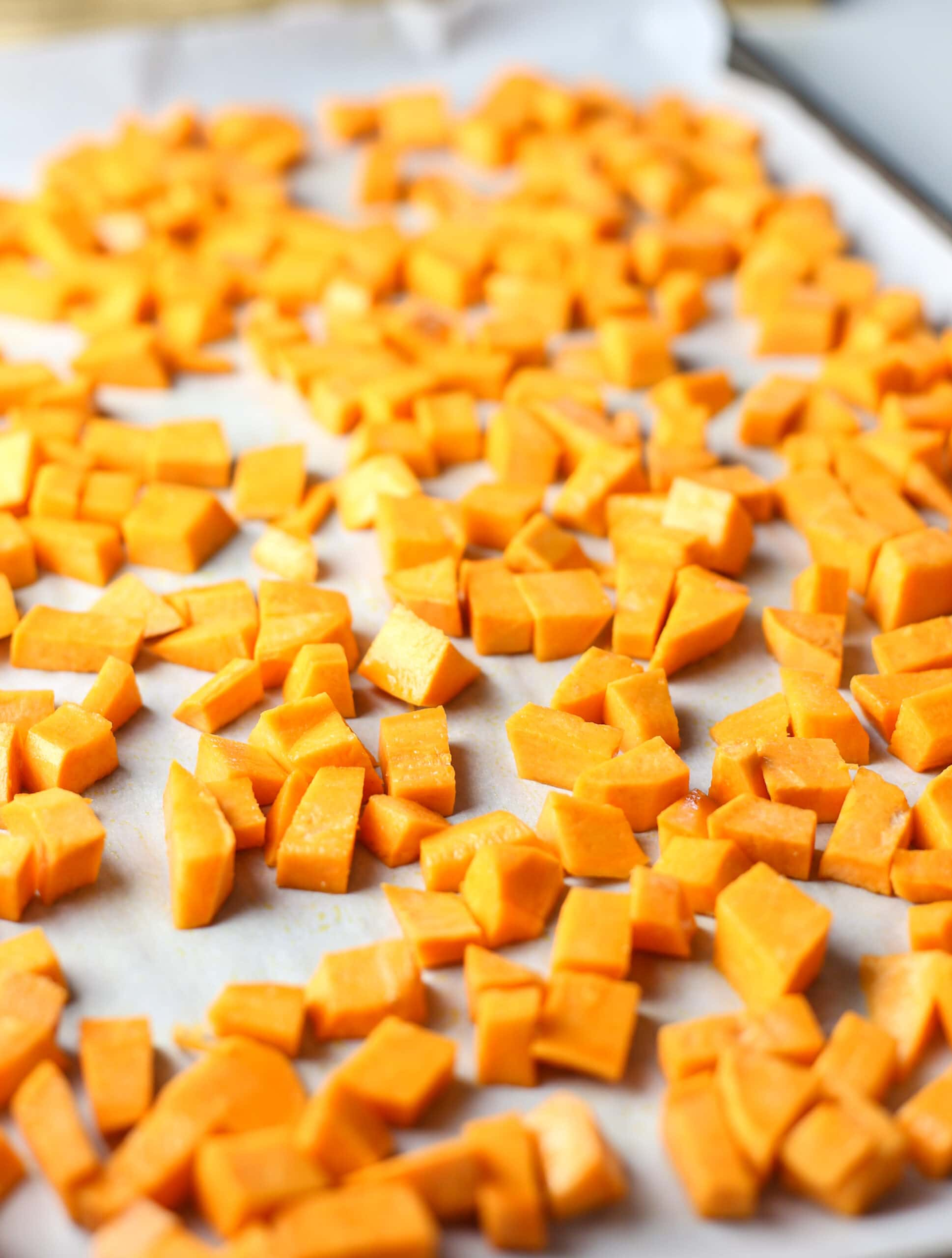 Chopped raw butternut squash on a parchment paper lined baking sheet.