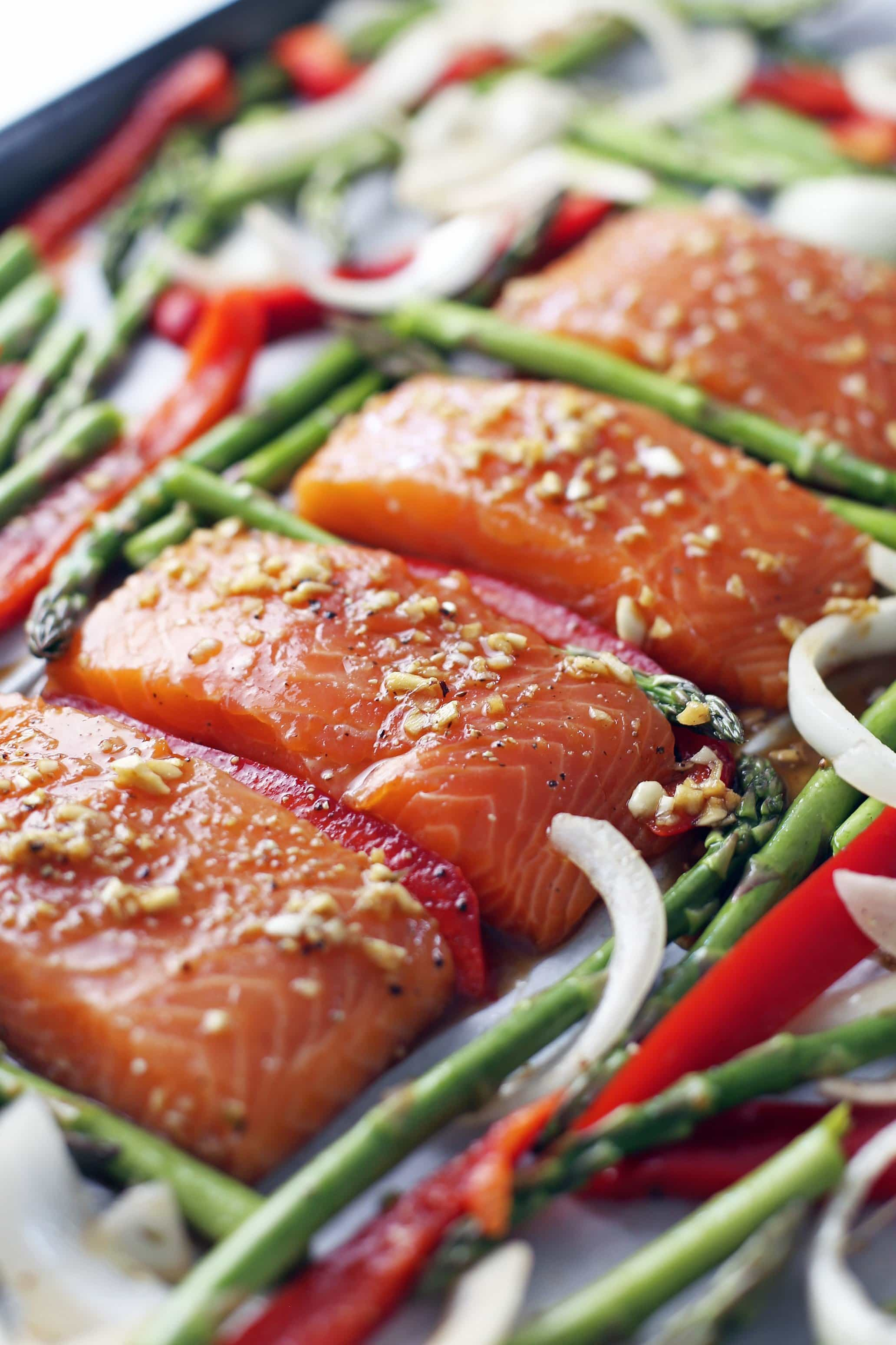 Four raw marinated salmon fillets in a row with asparagus, bell pepper, and onions surrounding them on a large baking sheet.