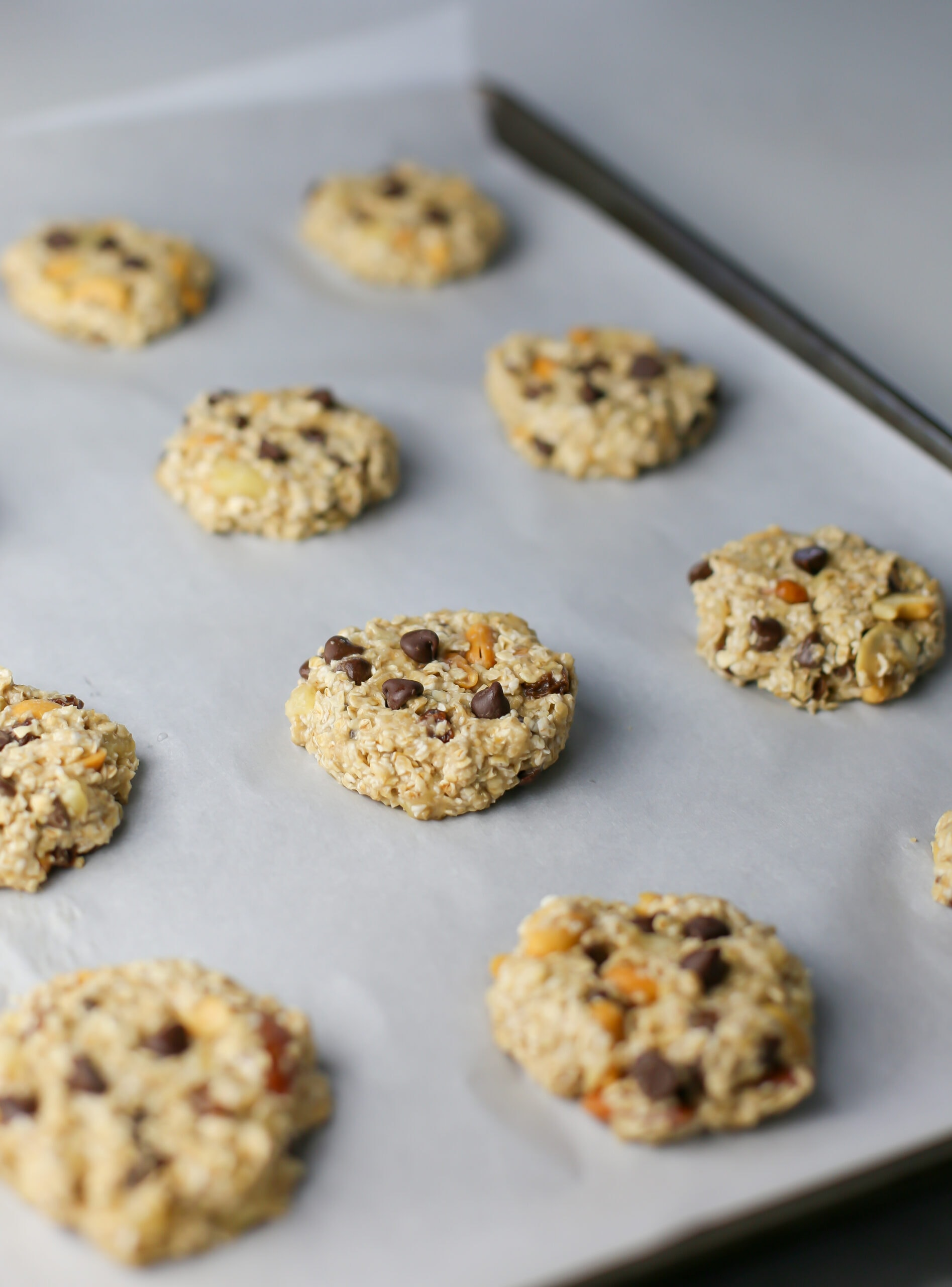 Unbaked trail mix cookies on a parchment paper lined baking sheet.