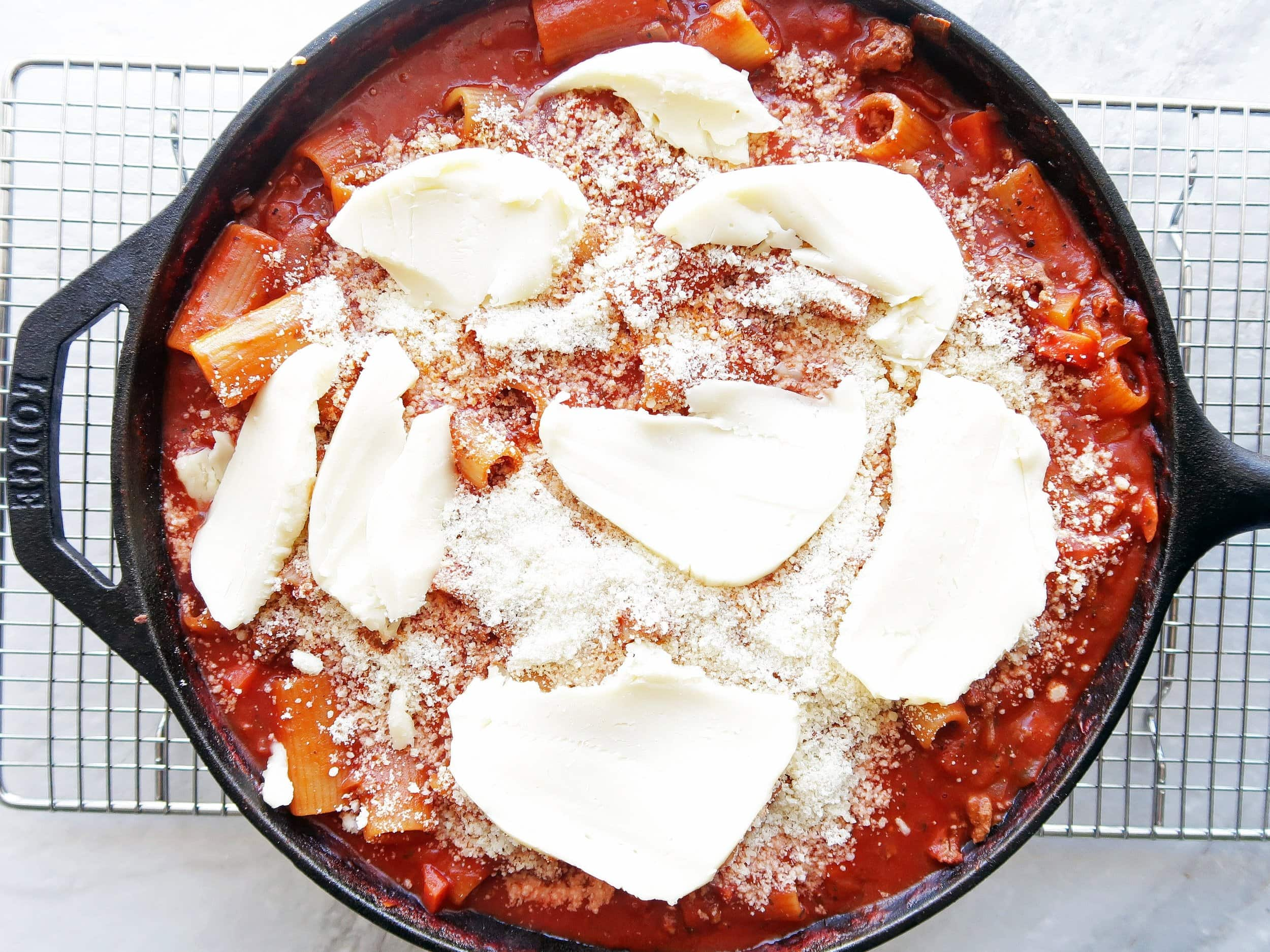 A cast iron skillet filled with rigatoni covered in meat sauce and topped with mozzarella and parmesan.