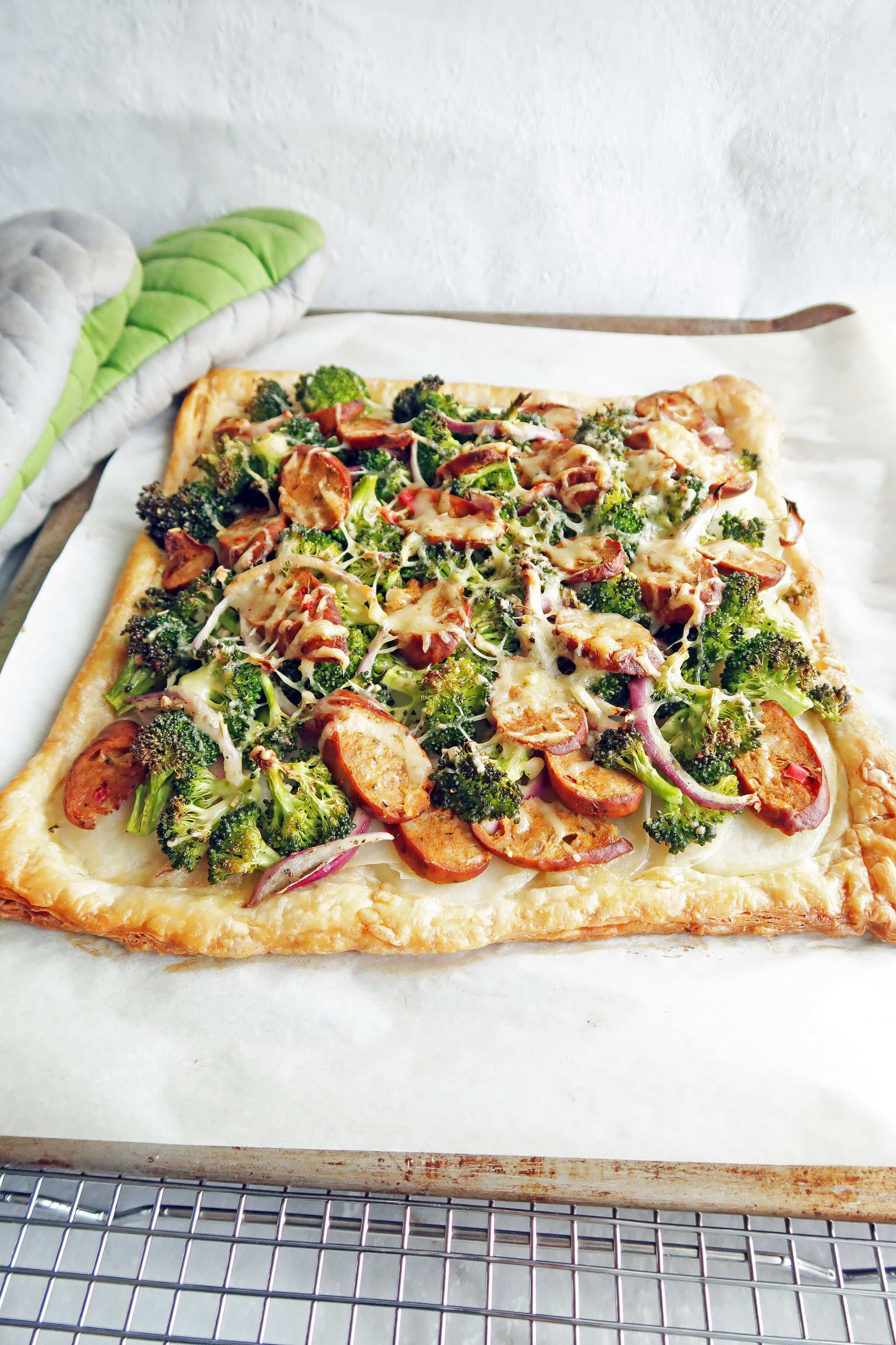 Roasted Broccoli Potato and Sausage Puff Pastry Tart on a parchment lined baking sheet.