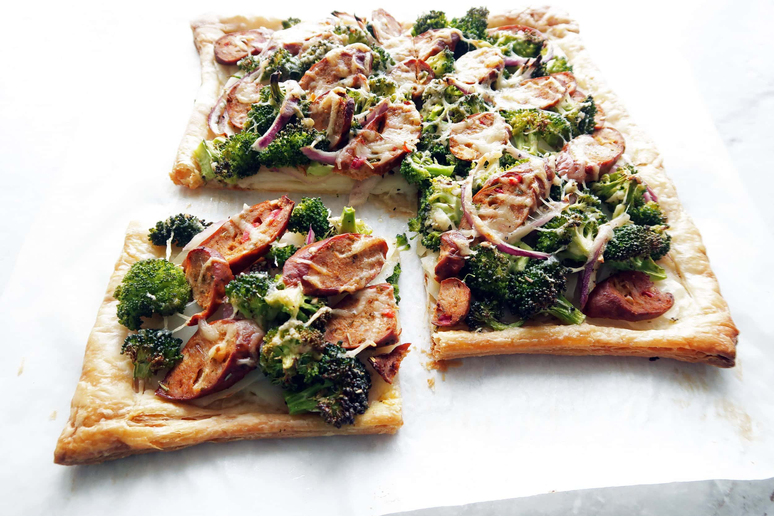 Roasted Broccoli Potato & Sausage Tart with one piece cut out; An easy to make puff pastry appetizer or dinner.