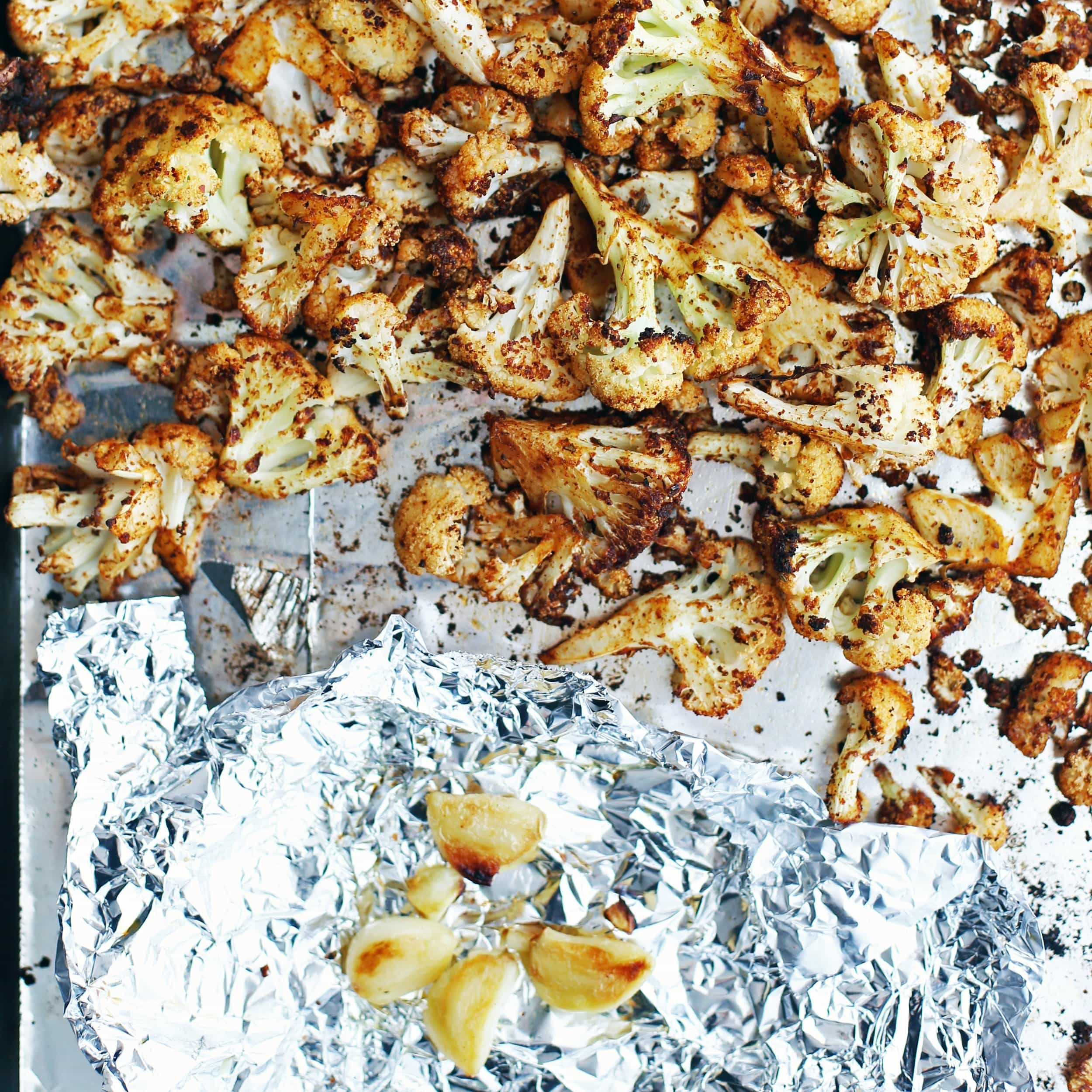 Roasted spiced cauliflower florets and roasted garlic cloves on a baking sheet.