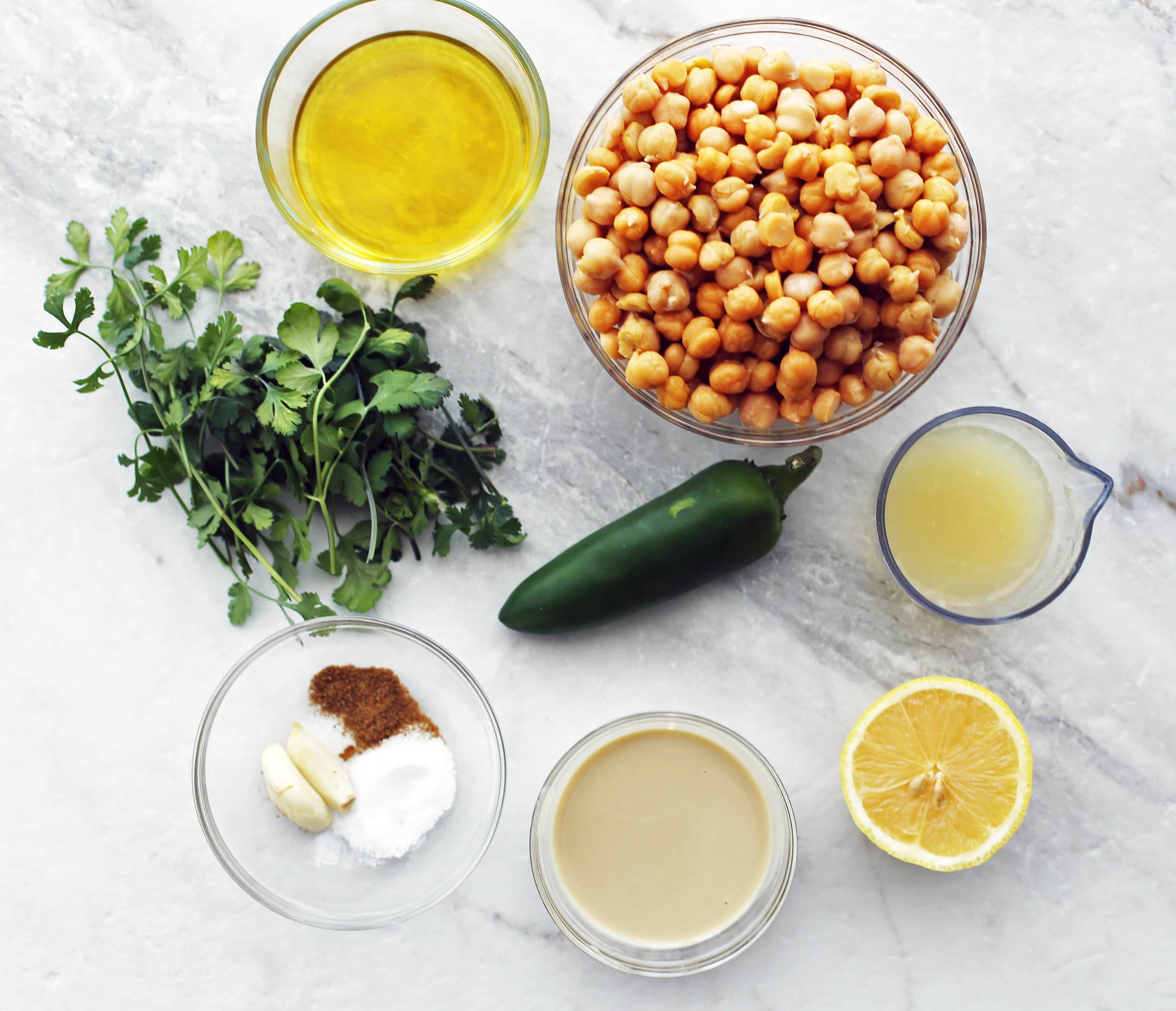An overhead view of cooked chickpeas, cilantro, jalapeno pepper, tahini, lemon, garlic, olive oil,cumin, and salt.