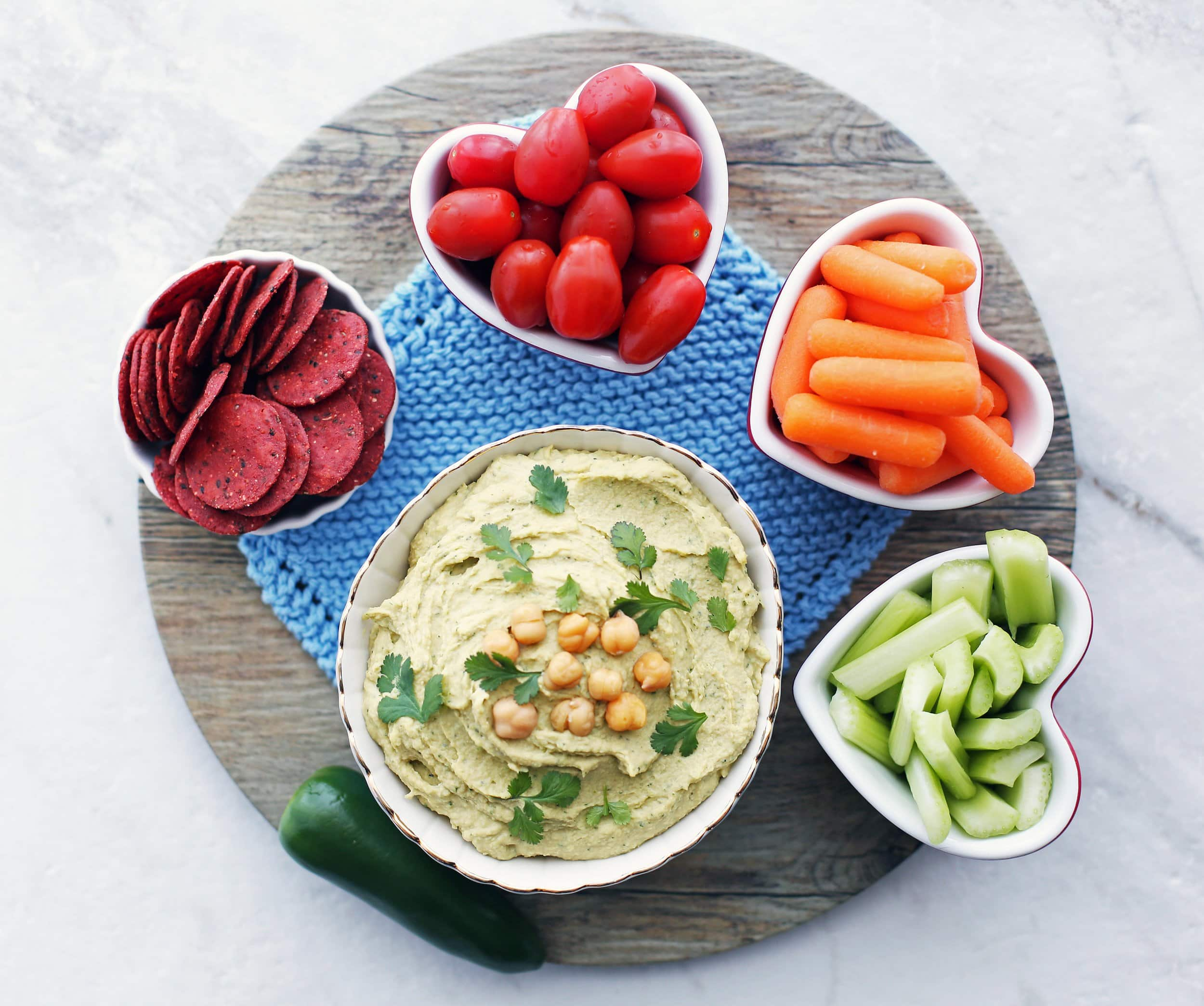 An overhead shot of a bowl of jalapeno cilantro hummus with carrots, tomatoes, celery, and crackers.