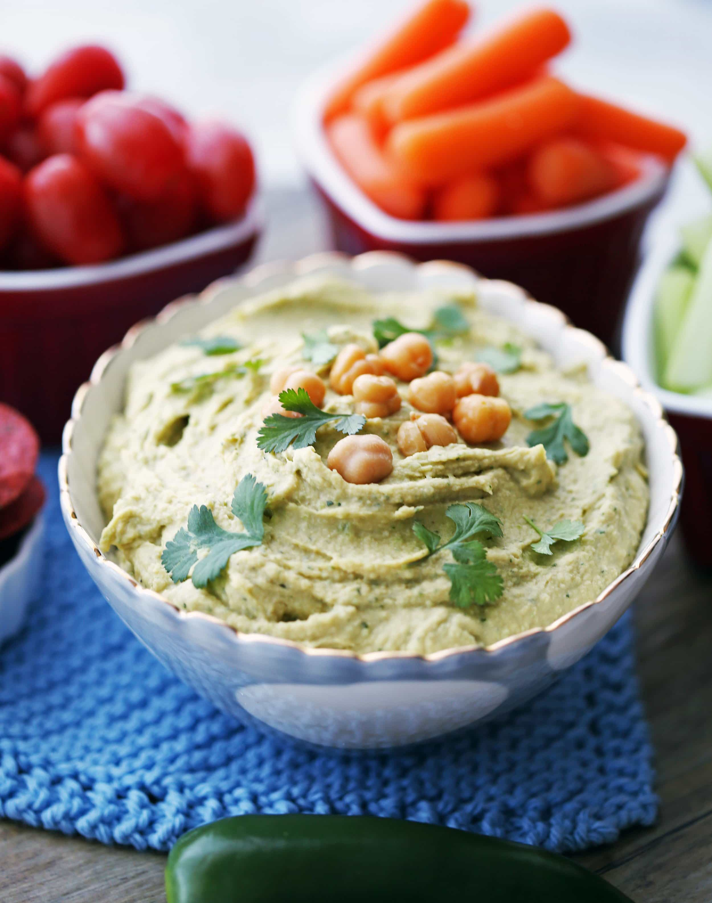 A closeup view of a bowl of jalapeno cilantro hummus with vegetables in the background.