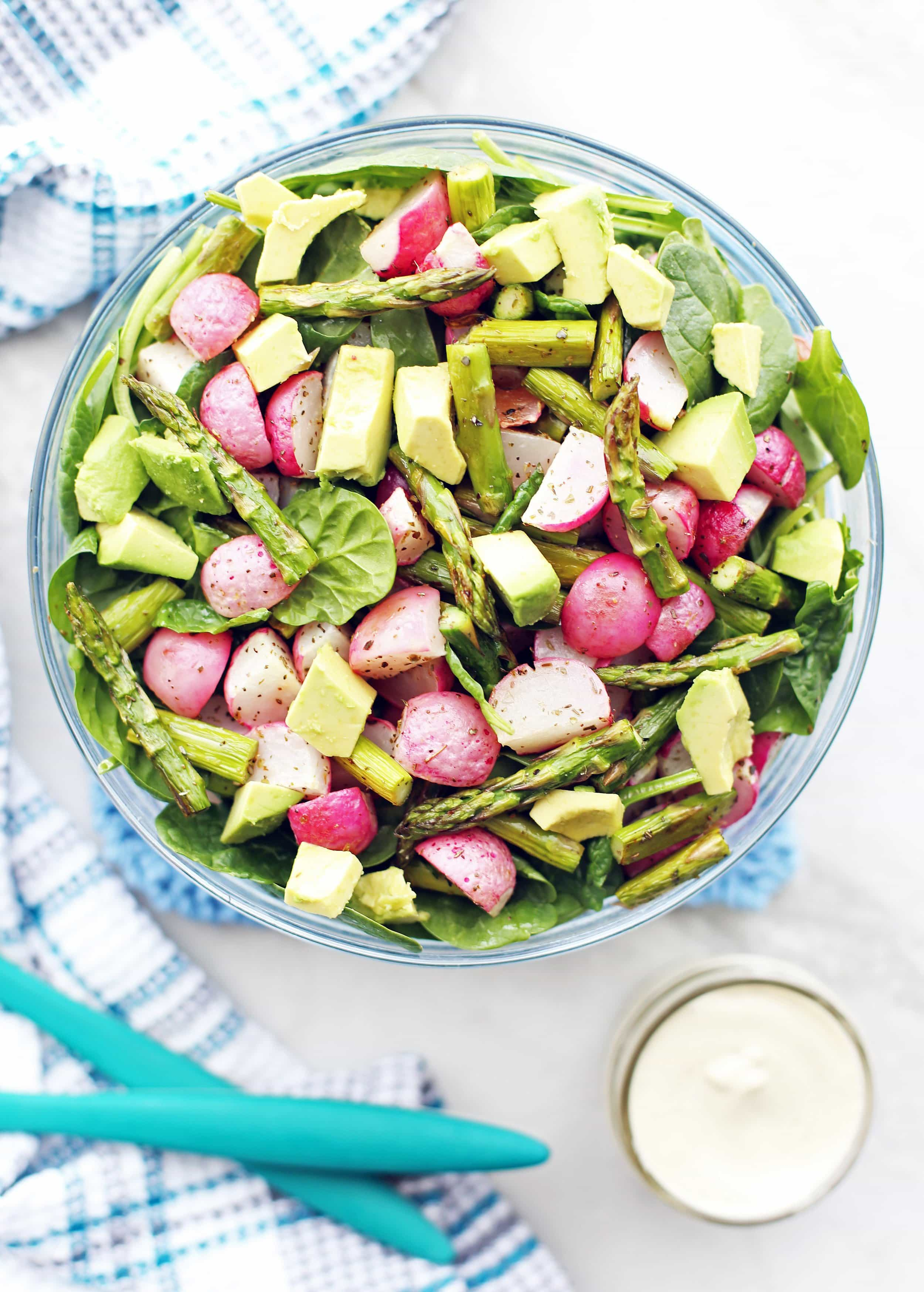 Overhead view of Roasted Asparagus and Radish Salad with spinach and avocado in a large glass bowl.