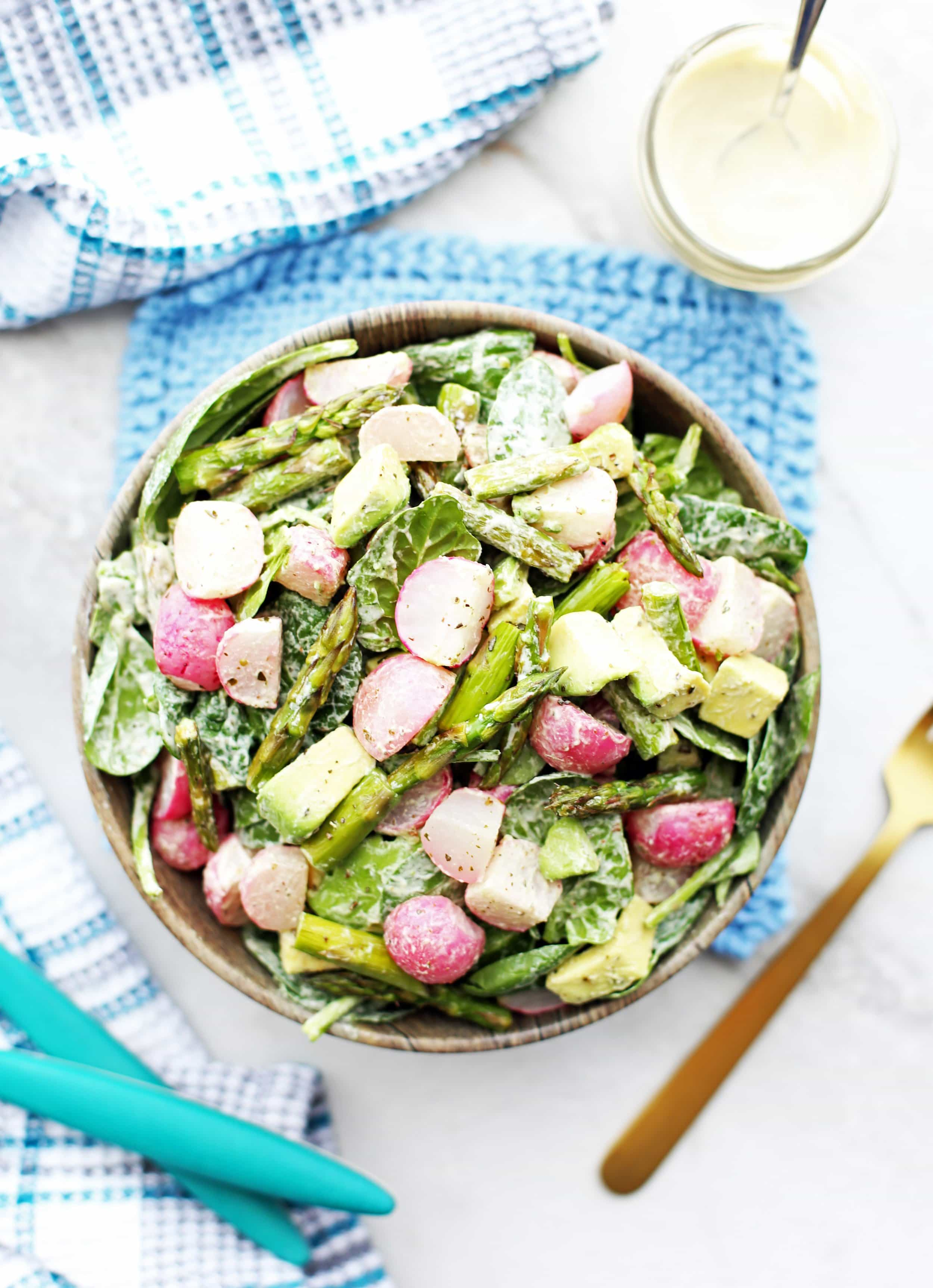 Overhead Roasted Asparagus and Radish Salad with Creamy Garlic Cashew Dressing in a wooden bowl.