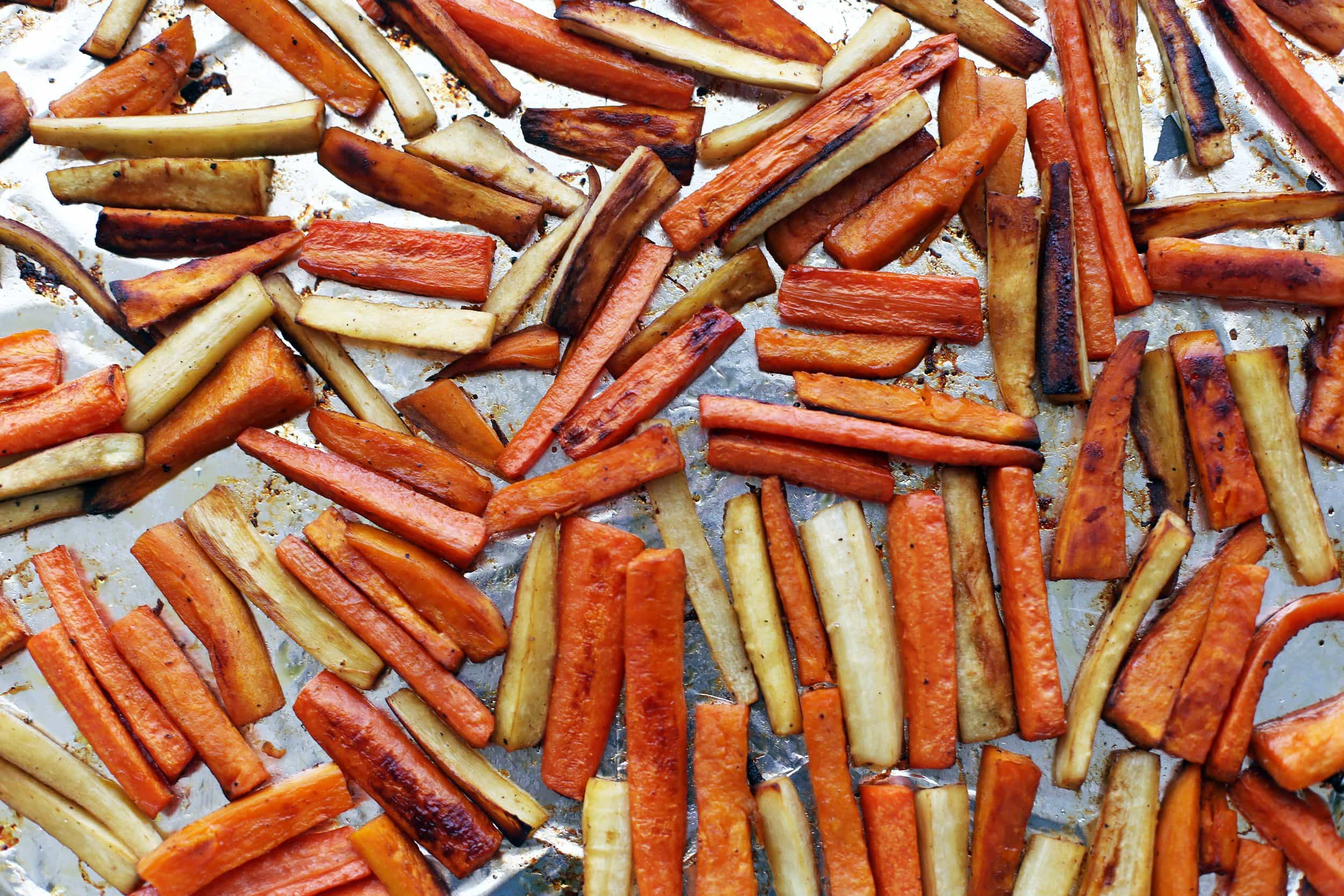 Roasted carrots, parsnips, and sweet potatoes in a single layer on an aluminum foiled lined baking sheet.