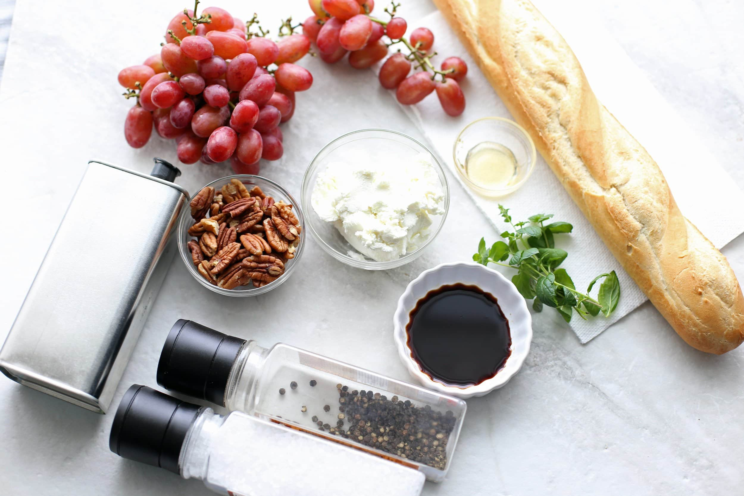 Overview of a baguette, red grapes, goat cheese, balsamic vinegar, fresh mint, pecans, olive oil, salt, and pepper.