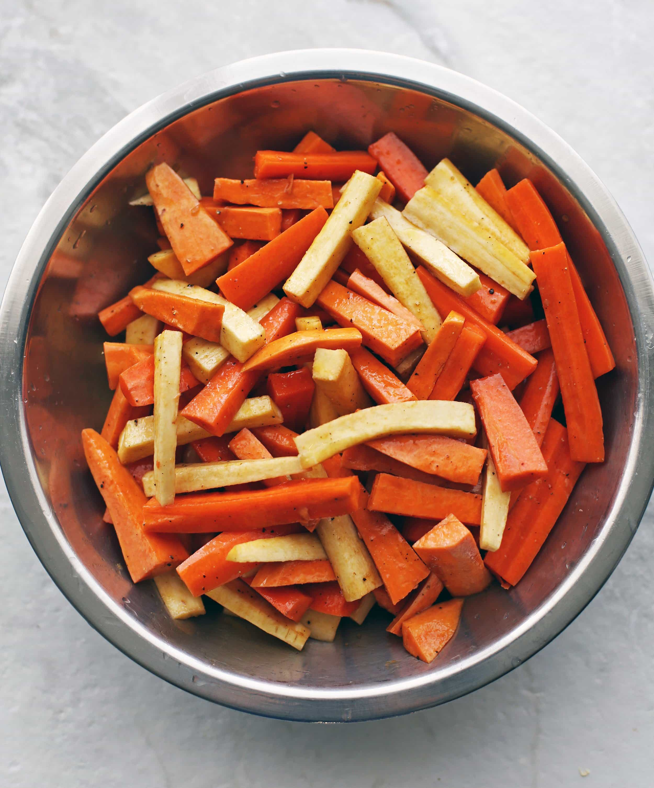 Sliced carrots, parsnips, and sweet potatoes mixed with olive oil and balsamic vinegar in a large metal bowl.
