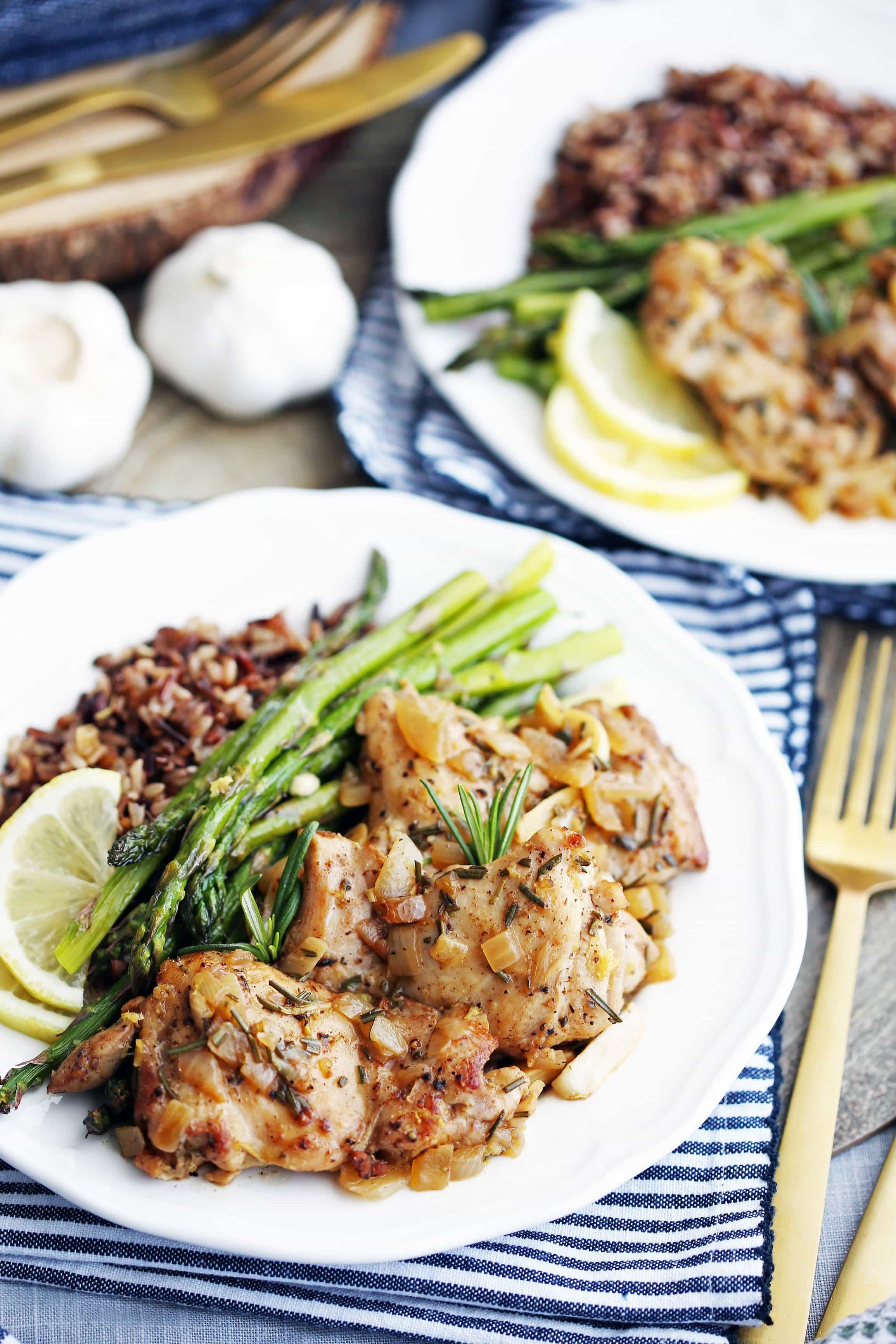 A white plate containing rosemary garlic chicken, roasted asparagus, and wild rice.