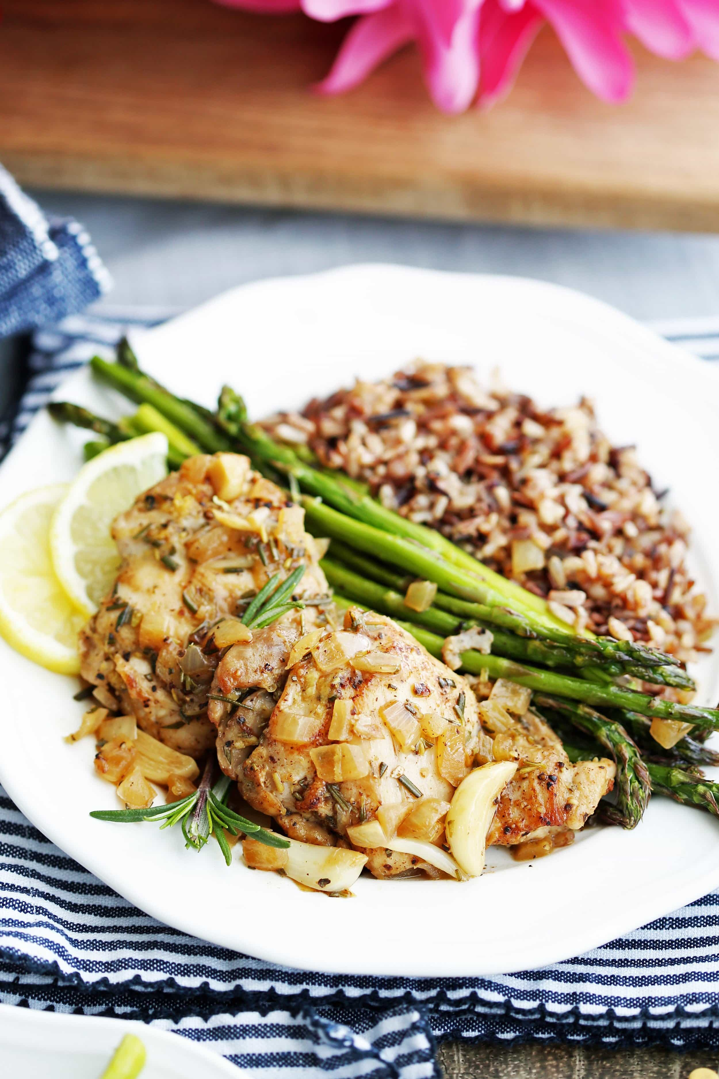 Two rosemary garlic chicken thighs, roasted asparagus, and wild rice on a white plate.