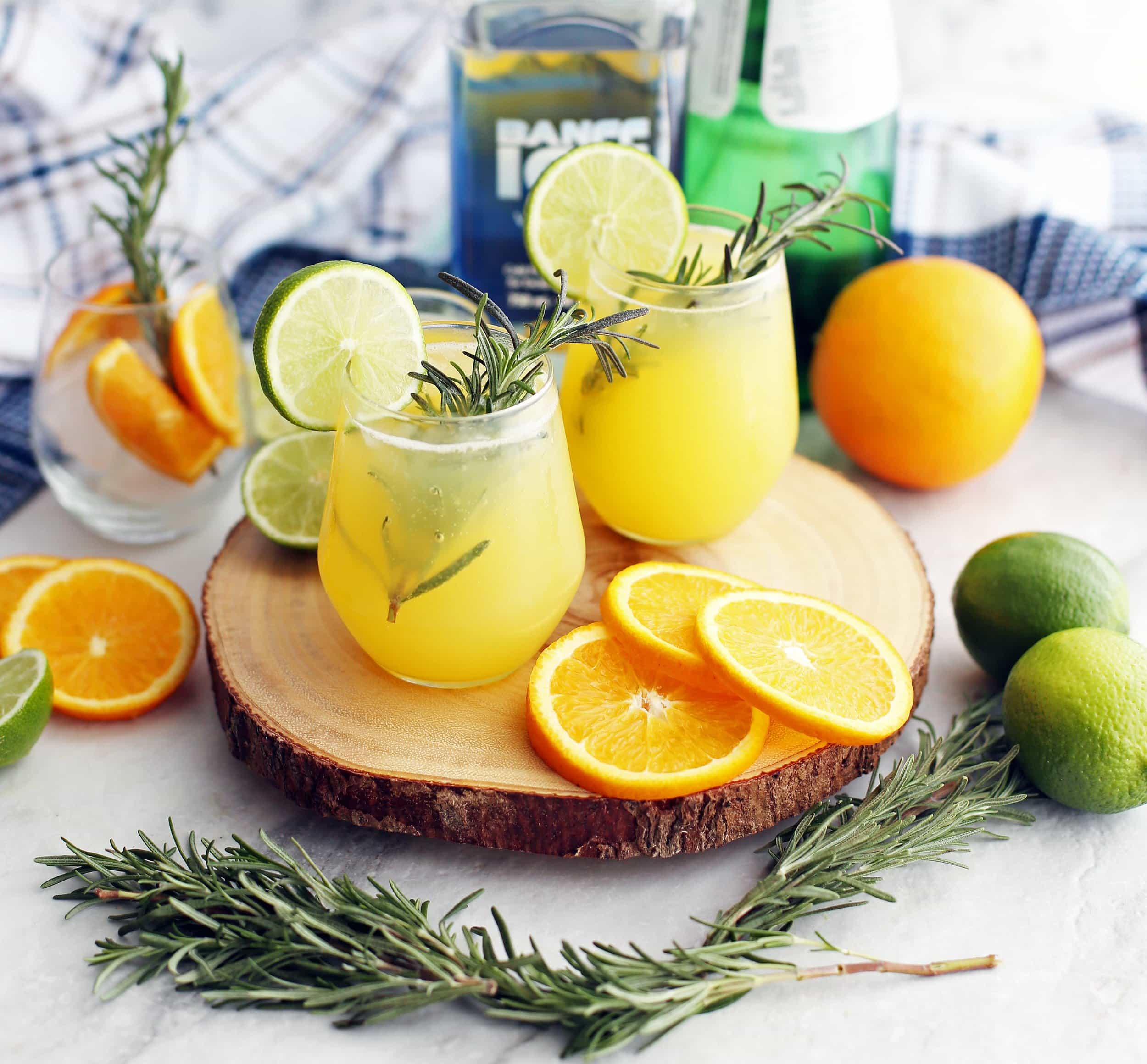 A side view of two glasses of sparkling maple orange vodka with fresh rosemary sprigs, lime slices,and orange slices.