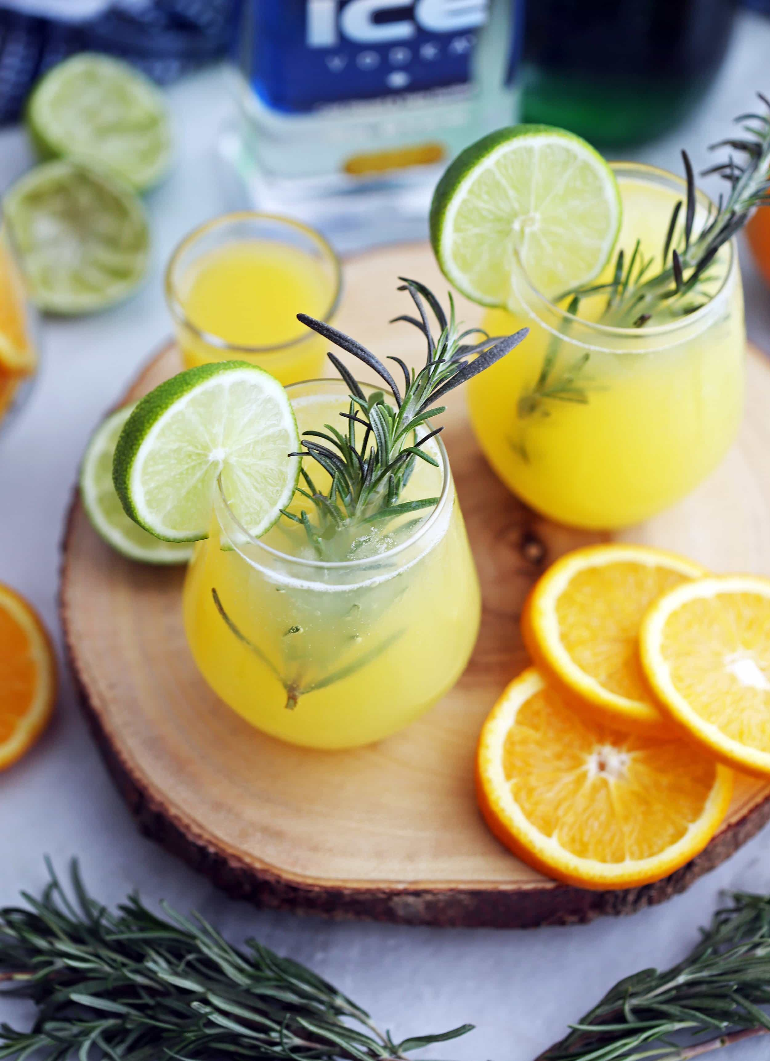 An high-angled view of two glasses of sparkling maple orange vodka with fresh rosemary sprigs, lime slices,and orange slices.